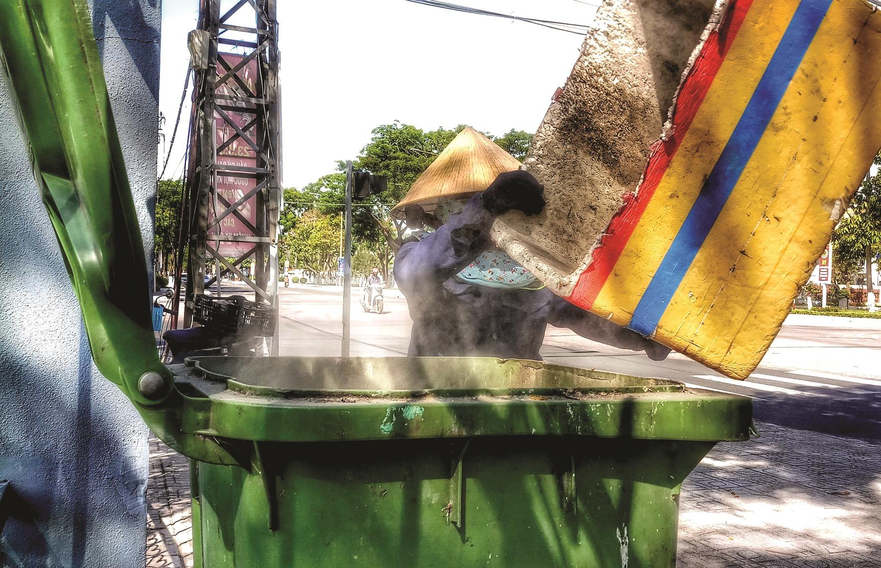 Rác từ xe đẩy sẽ được đổ vào những chiếc thùng đặt dọc tuyến đường. Bụi bặm, nhọc nhằn nhưng vì mưu sinh nên họ cố gắng vượt qua.
