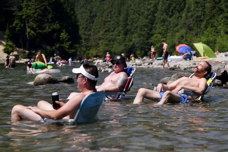 Trong khi nhiều người ngâm mình dưới hồ nước Alouette để giải nhiệt. Ảnh: Reuters