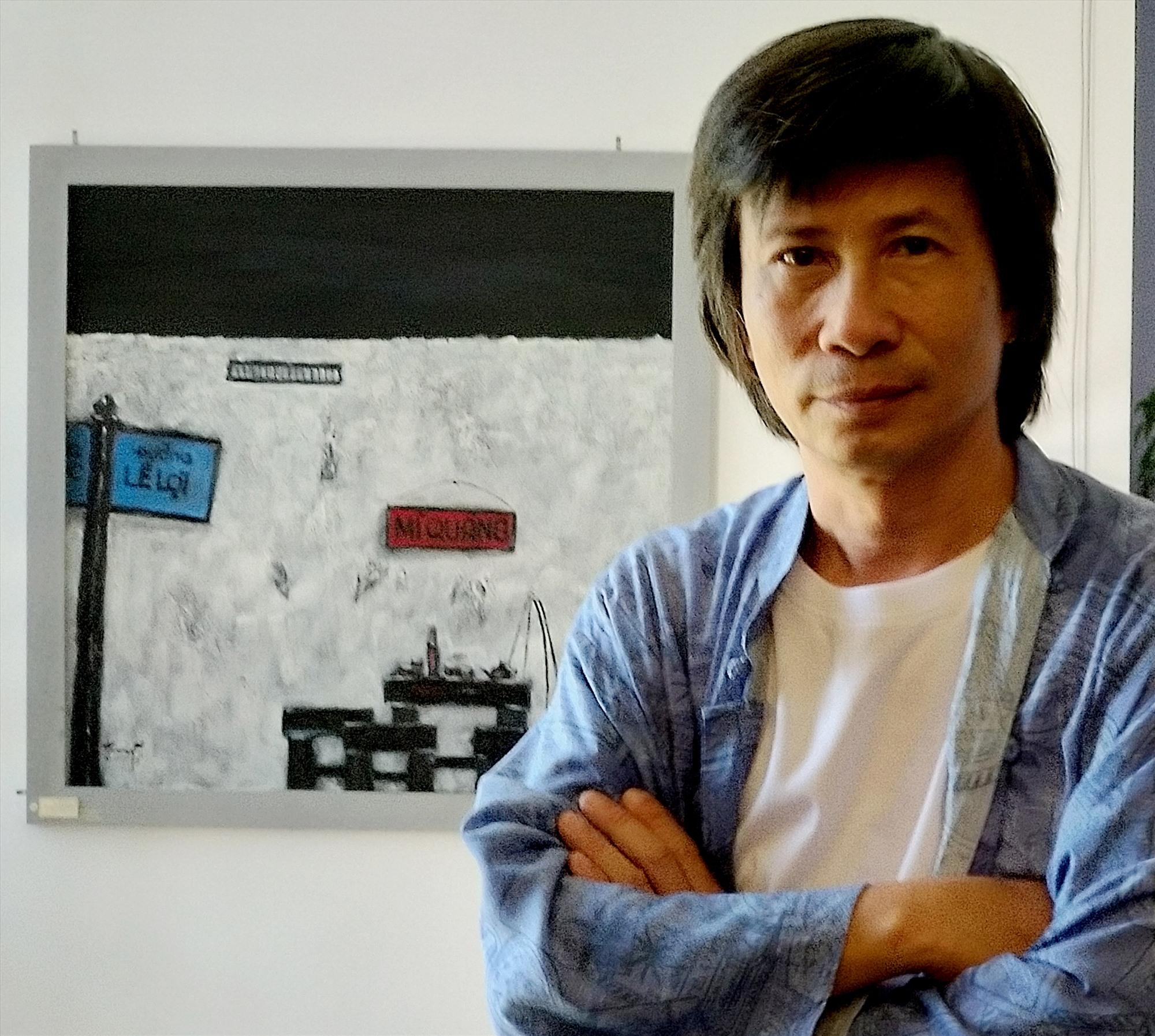 """Họa sĩ Trương Bách Tường và bức tranh """"Góc phố"""" treo trên tường phía sau."""
