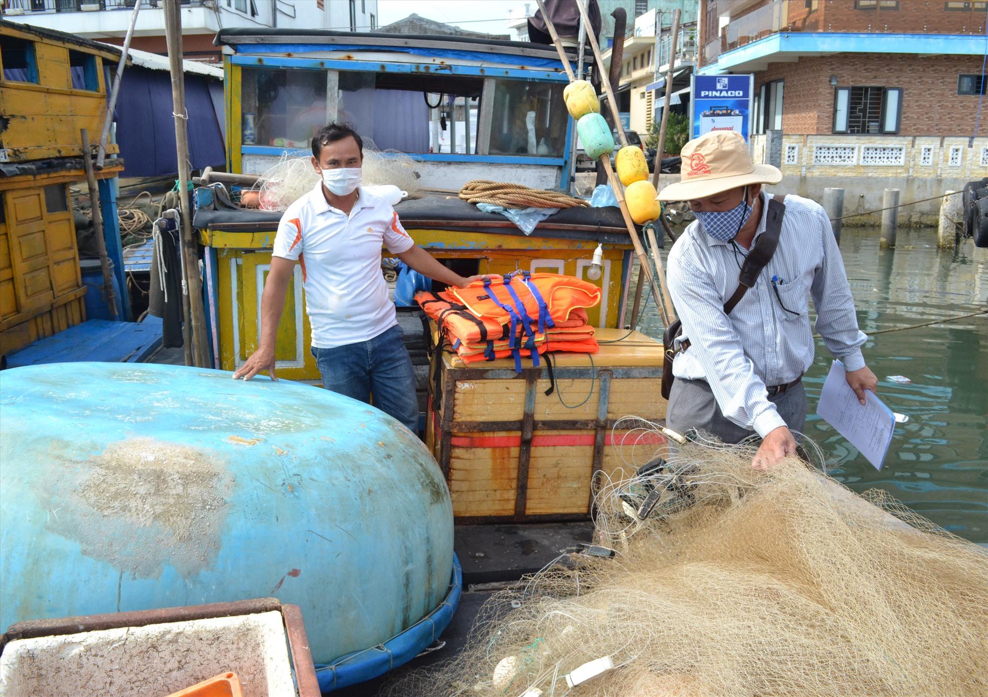 Đăng kiểm viên là cán bộ Chi cục Thủy sản Quảng Nam thực hiện đăng kiểm trên tàu cá của ngư dân huyện Núi Thành. Ảnh: VIỆT NGUYỄN