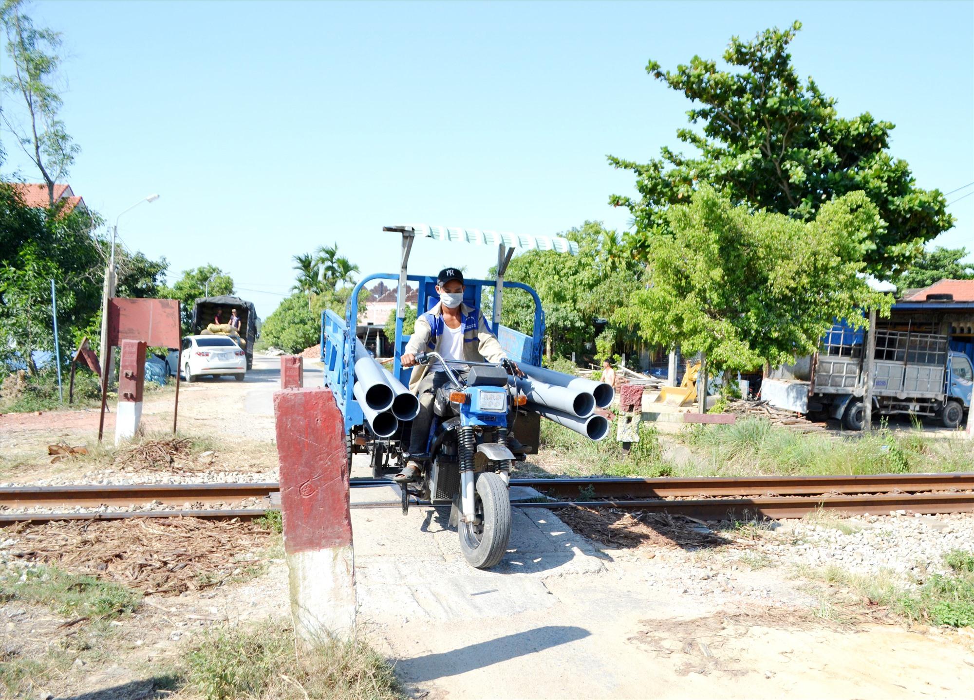 Người dân tháo dỡ trụ bê tông tại lý trình đường sắt km845+875 (xã Bình Chánh, Thăng Bình) để xe 3 bánh qua lại. Ảnh: C.T