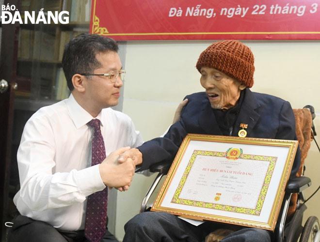 Bí thư Thành ủy Nguyễn Văn Quảng (bên trái) trao Huy hiệu 80 năm tuổi Đảng cho đồng chí Trần Thận, ngày 22.3.2021. Ảnh: ĐẶNG NỞ