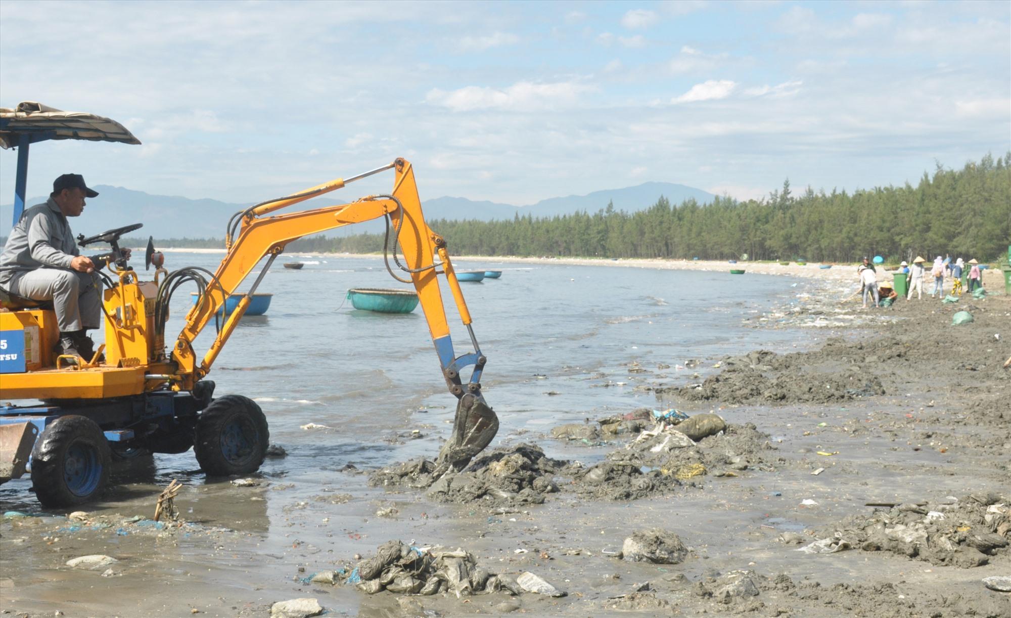 Nhân viên môi trường trục với, thu gom rác thải nhựa tại bờ biển xã đảo Tam Hải. Ảnh: N.Đ