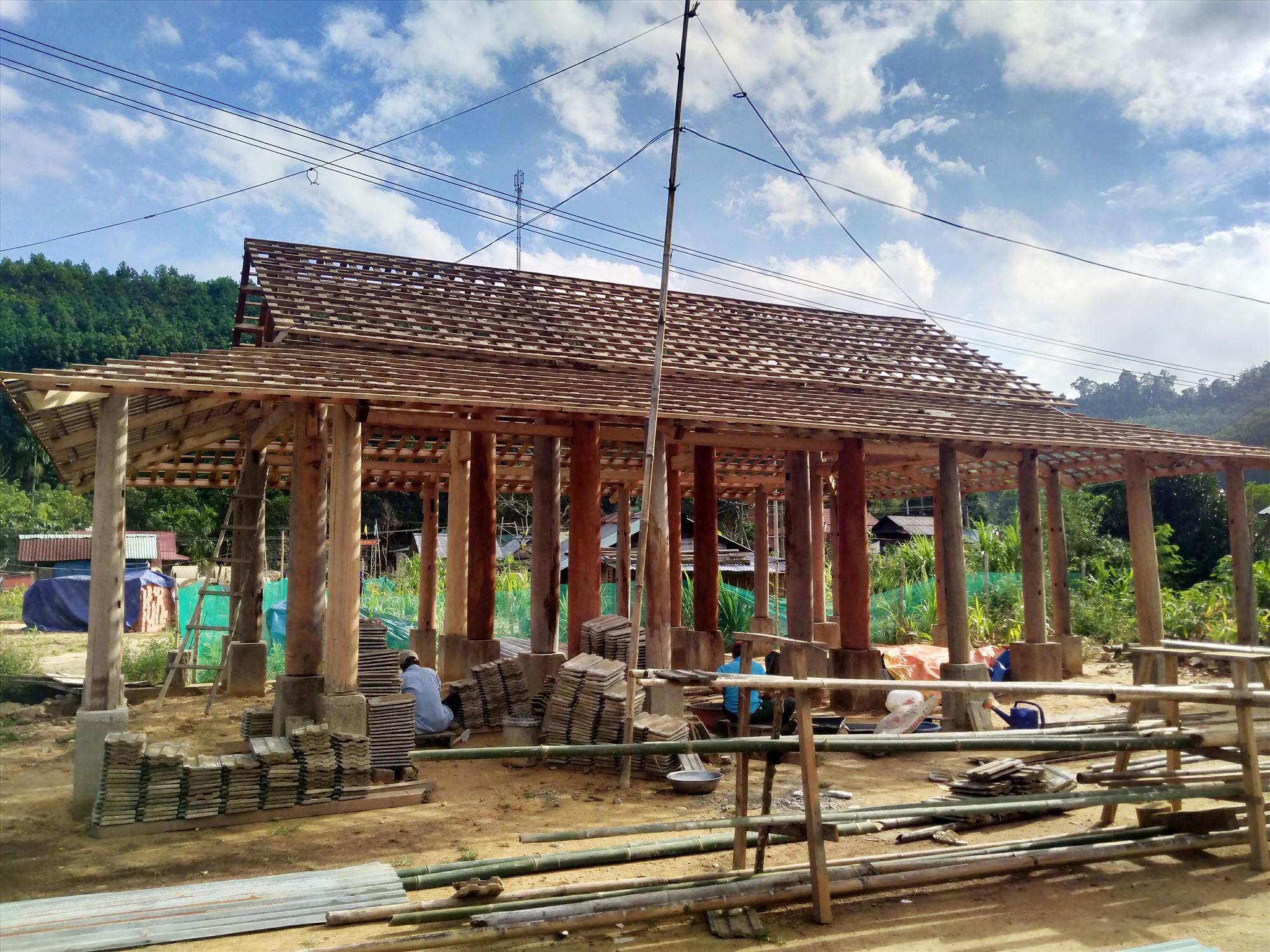 Một hộ dân đang dựng nhà tại khu dân cư mới thôn Adzốc (xã Bhalêê). Ảnh: N.Đ