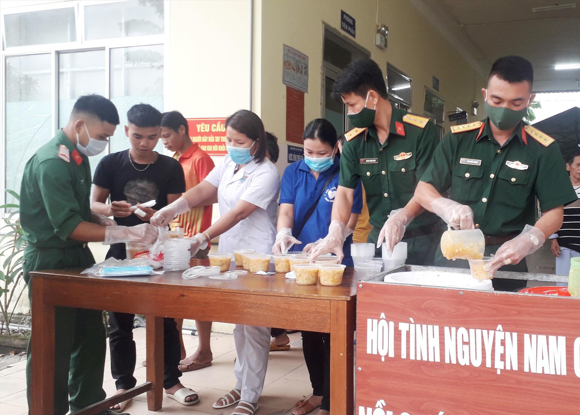 Đoàn viên thanh niên Chi đoàn Cơ quan quân sự huyện Nam Giang chuẩn bị cháo phát cho bệnh nhân. Ảnh: V.T