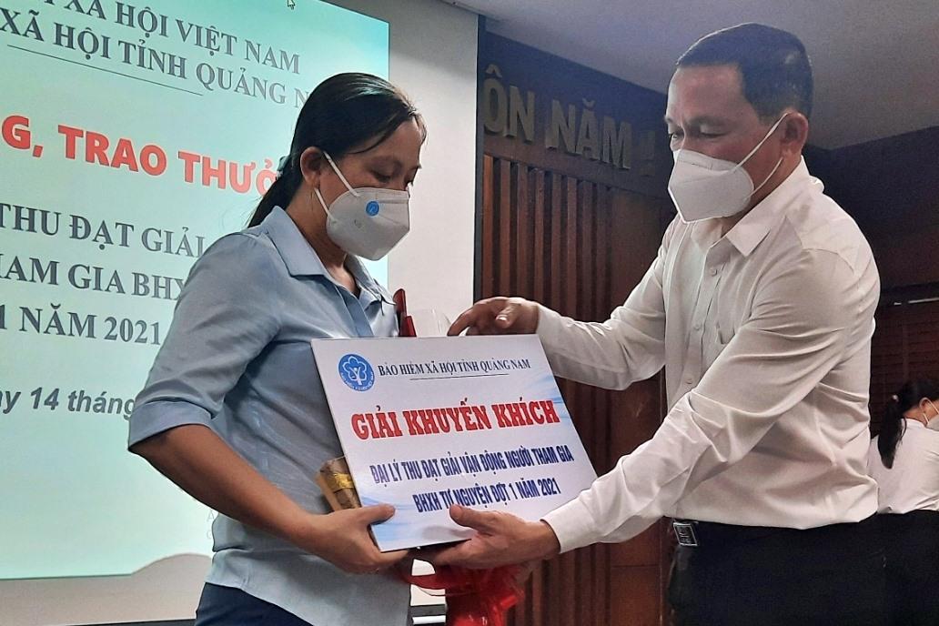 Giám đốc BHXH Quảng Nam Nguyễn Thanh Danh khen thưởng các đại lý thu hoàn thành xuất sắc nhiệm vụ phát triển đối tượng tham gia BHXH tự nguyện. Ảnh: H.Đ