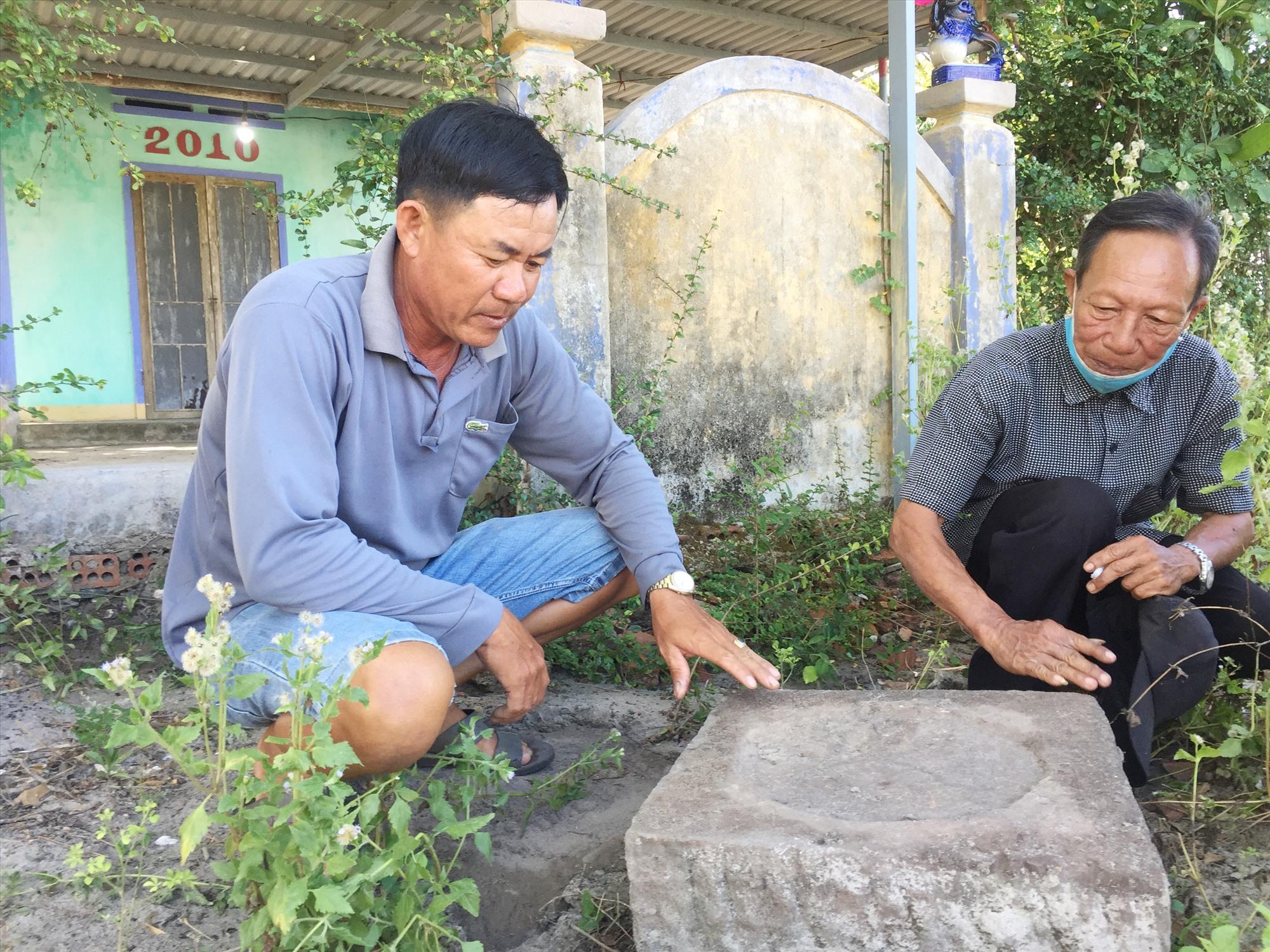 Ông Nguyễn Xuân Thập (bên phải) lật tảng đá là chân tán của cột đình Trà Luông.