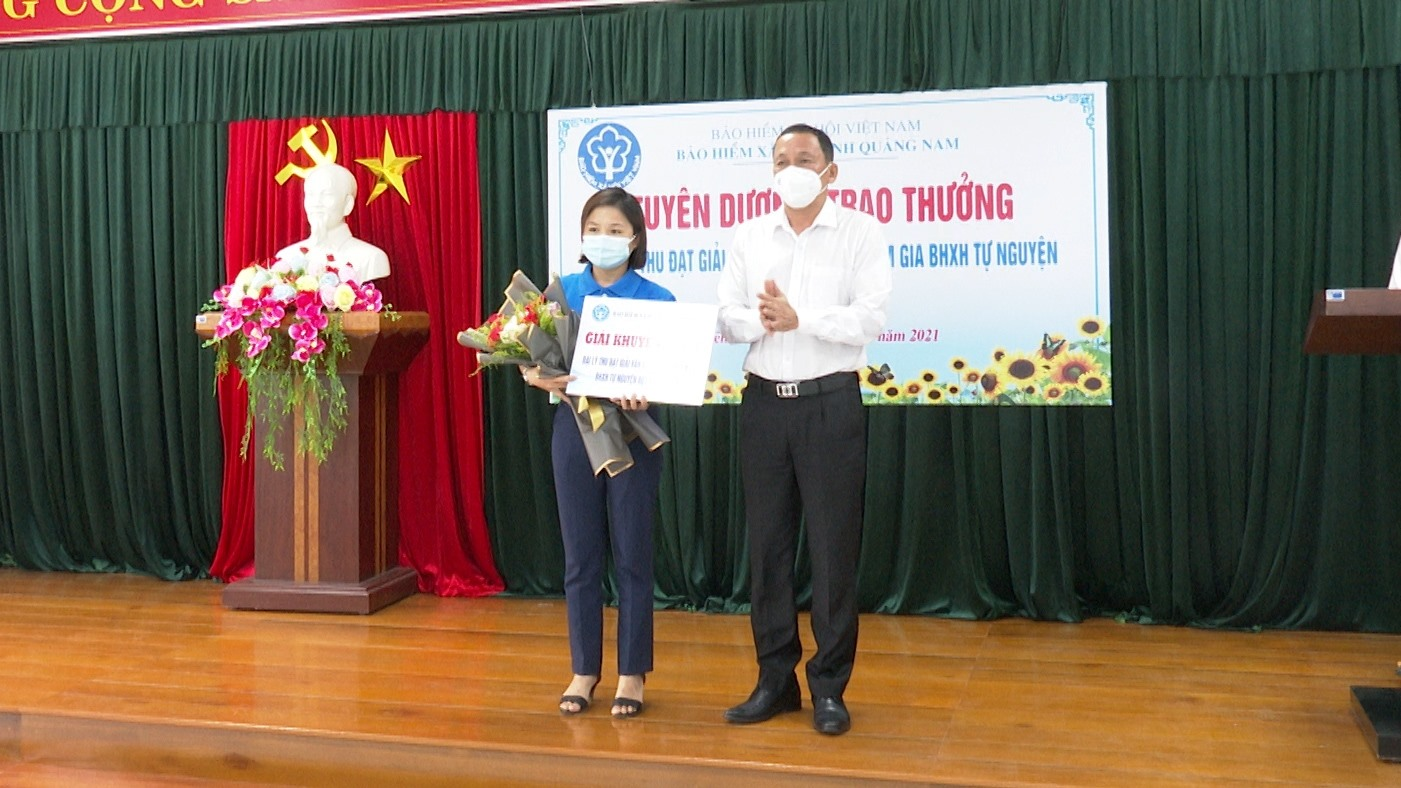 Giám đốc BHXH tỉnh Nguyễn Thanh Danh trao giải cho đại lý thu Đinh Thị Lợi. Ảnh: N.H