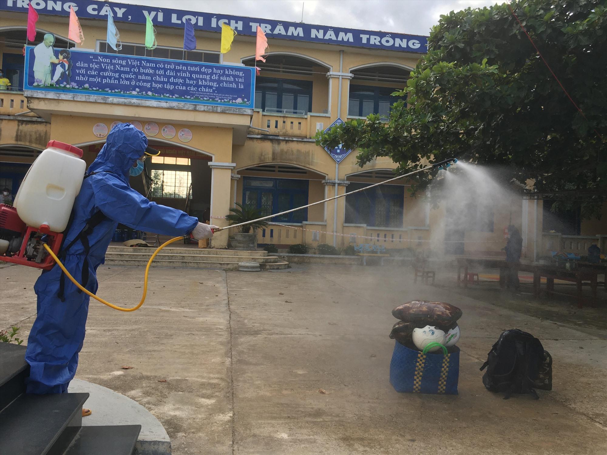 Phun khử trùng hành lý người cách ly y tế tập trung tại trường Tiểu học Nguyễn Duy Hiệu (Phú Ninh). Ảnh: C.Đ