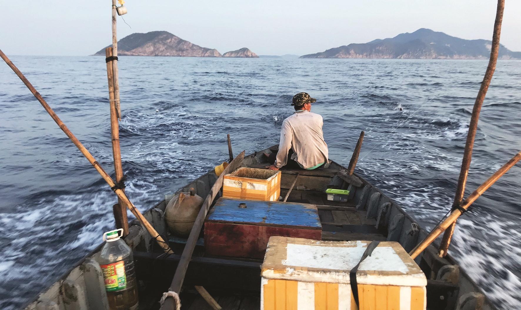 Ngư dân điều khiển tàu chạy và theo dõi cá cắn câu.