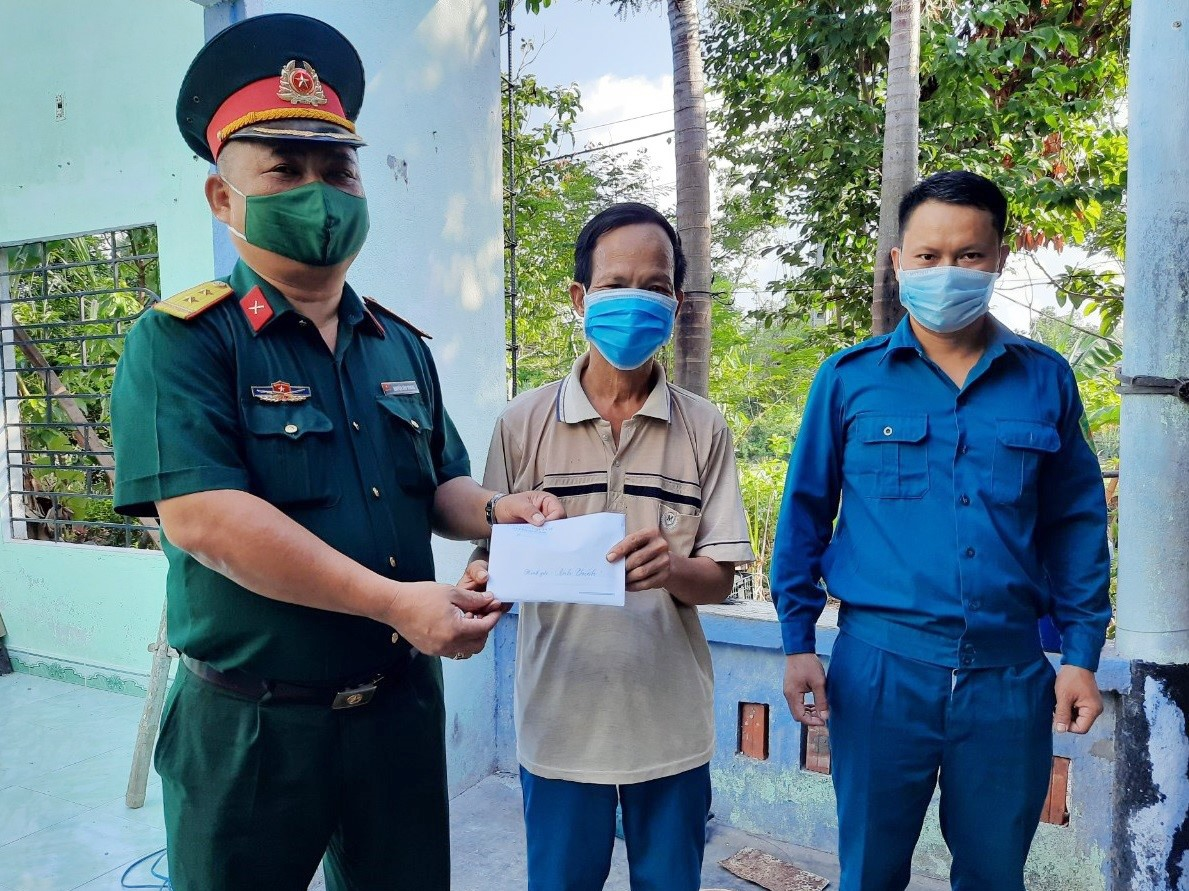Đại diện Ban CHQS huyện Quế Sơn hỗ trợ 40 triệu đồng cho ông Nguyễn Thanh Chính (xã Quế Phong). Ảnh: T.P