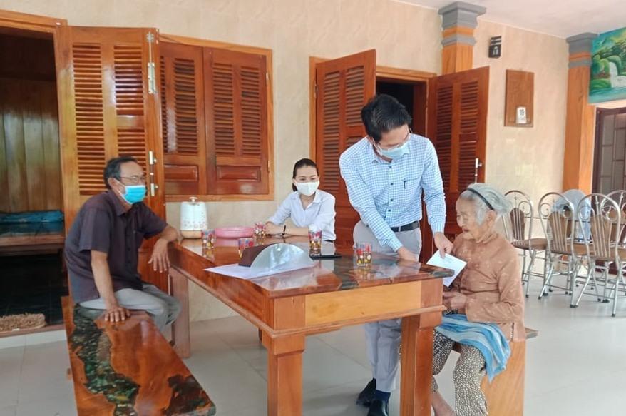 Lãnh đạo huyện Hiệp Đức tặng quà Mẹ Việt Nam anh hùng. Ảnh: LINH NHI