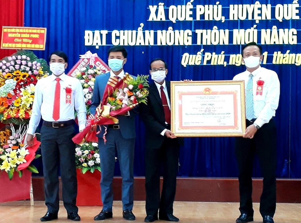Thừa ủy quyền của UBND tỉnh, lãnh đạo huyện Quế Sơn trao bằng công nhận xã đạt chuẩn NTM nâng cao năm 2020 cho lãnh đạo xã Quế Phú vào sáng nay 21.7. Ảnh: N.S
