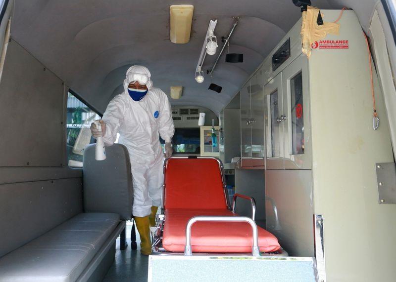 Một tình nguyện viên phun thuốc sát khuẩn trước và sau khi vận chuyển bệnh nhân Covid-19 ở Jakarta. Ảnh: Reuters
