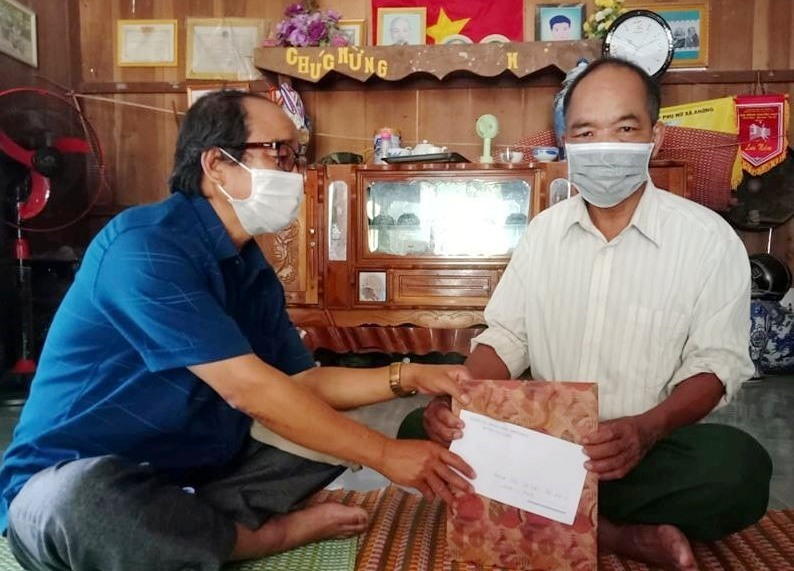 Ông Cơ Lâu Hạnh - Chủ tịch Ủy ban MTTQ Việt Nam huyện Tây Giang đến thăm hỏi tặng quà ông Blúp Sơn là đối tượng chính sách tiêu biểu ( thôn Anonh, xã A Nông). Ảnh H.Thúy