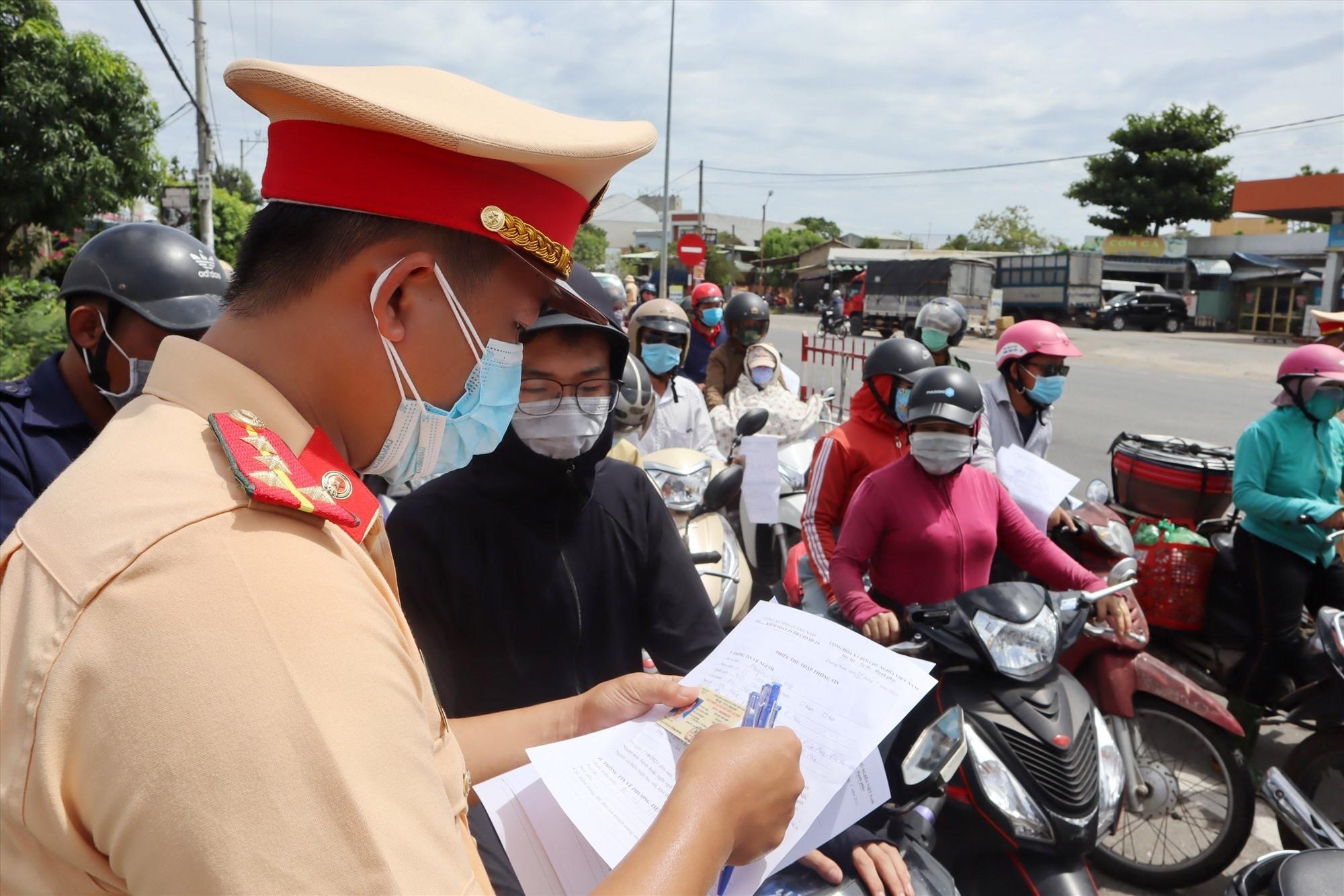 Lực lượng chức năng kiểm tra kỹ càng các giấy tờ để sàng lọc trường hợp được qua chốt. Ảnh: Q.T