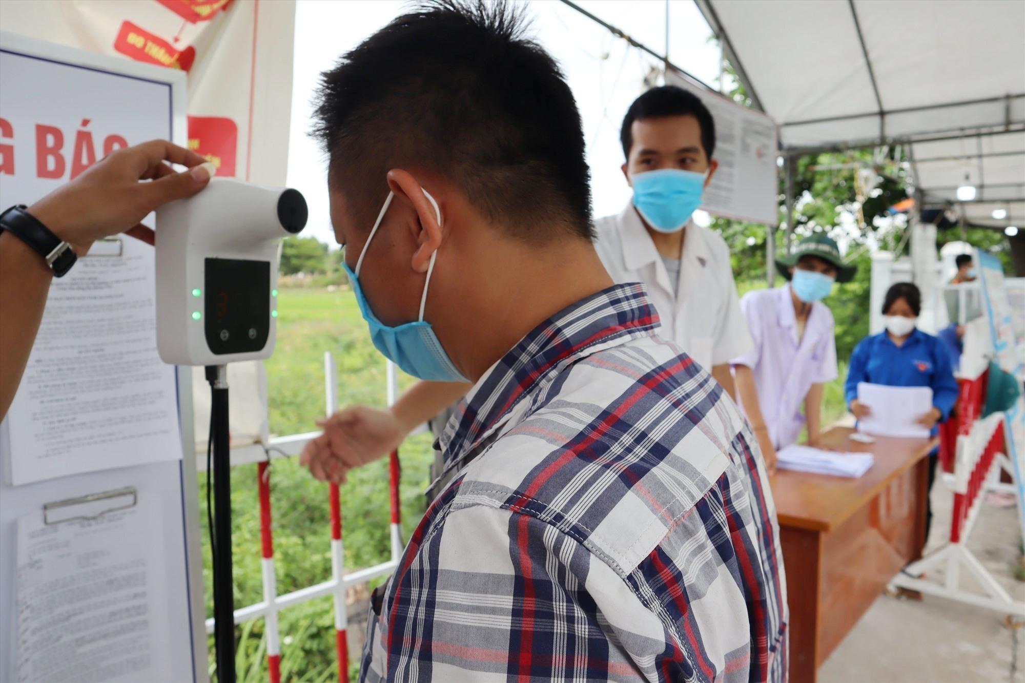 Sau khi qua chốt kiểm soát, người dân phải tiến hành các thủ tục khai báo y tế. Ảnh: Q.T