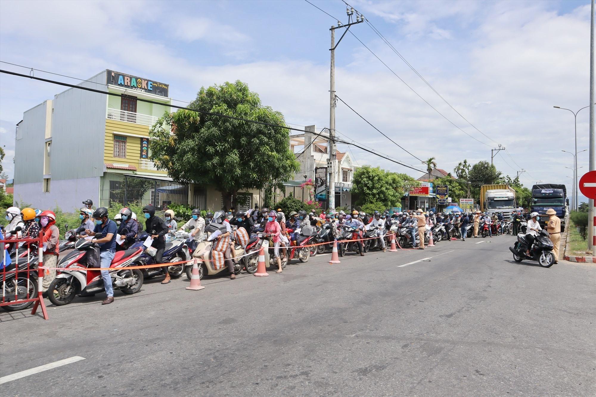 Đến 11 giờ trưa nay, vẫn còn hàng trăm người dân nối đuôi nhau chờ qua chốt để về Quảng Nam. Ảnh: Q.T