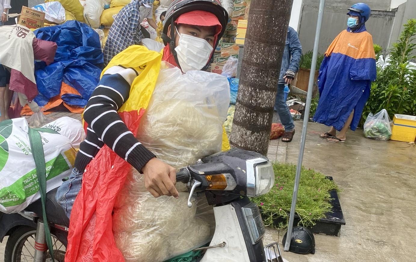 Cùng với việc đón người về, các chuyến xe chở theo lương thực thực phẩm để hỗ trợ bà con tại TP.Hồ Chí Minh. Người dân đến tại điểm tập kết để nhận hàng viện trợ từ quê nhà. Ảnh; Công Khanh