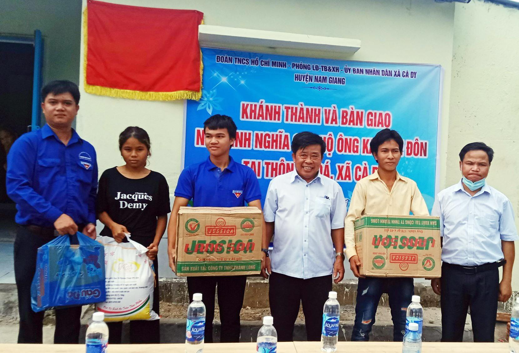 Đại diện người thân cụ Ka Hiên Đôn nhận quà hỗ trợ từ chính quyền địa phương trong ngày bàn giao nhà mới. Ảnh: Đ.N