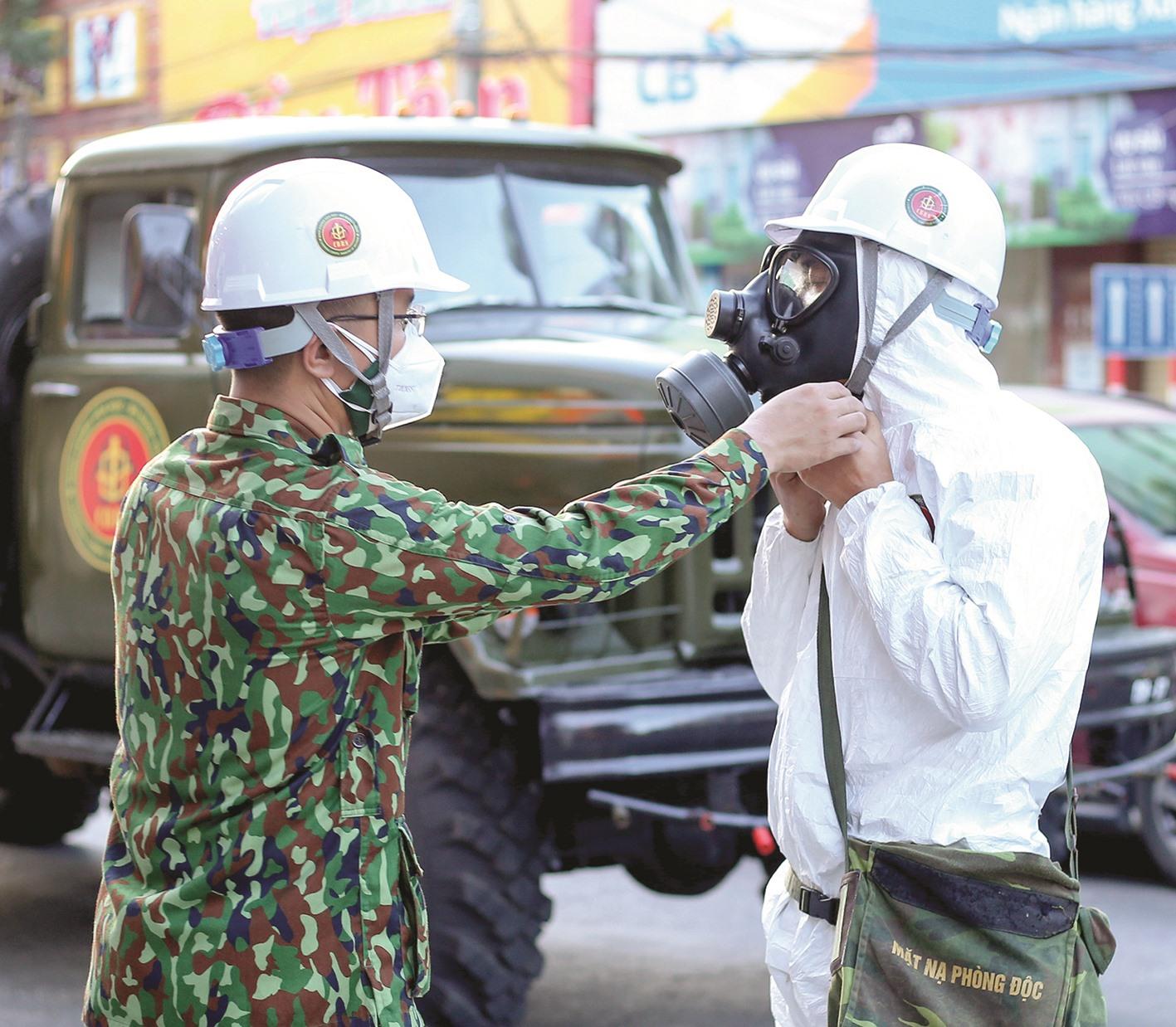 Giúp nhau mang đồ bảo hộ trước khi vào khu vực phun hóa chất.