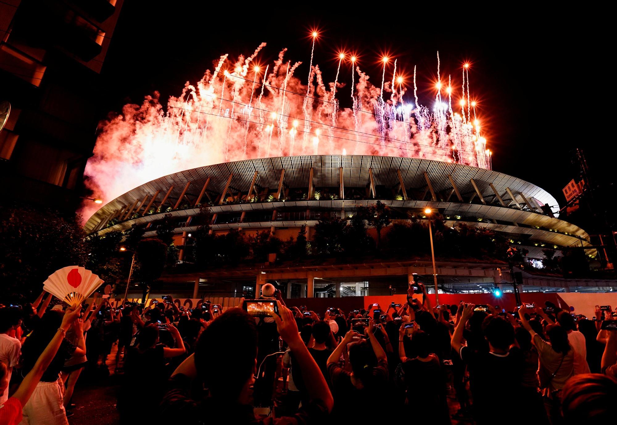 Không được vào sân để trực tiếp theo dõi buổi lễ khai mạc, nhiều người vẫn háo hức ghi lại những hình ảnh ngoạn mục ngay từ bên ngoài sân vận động Olympic. Ảnh: Reuters