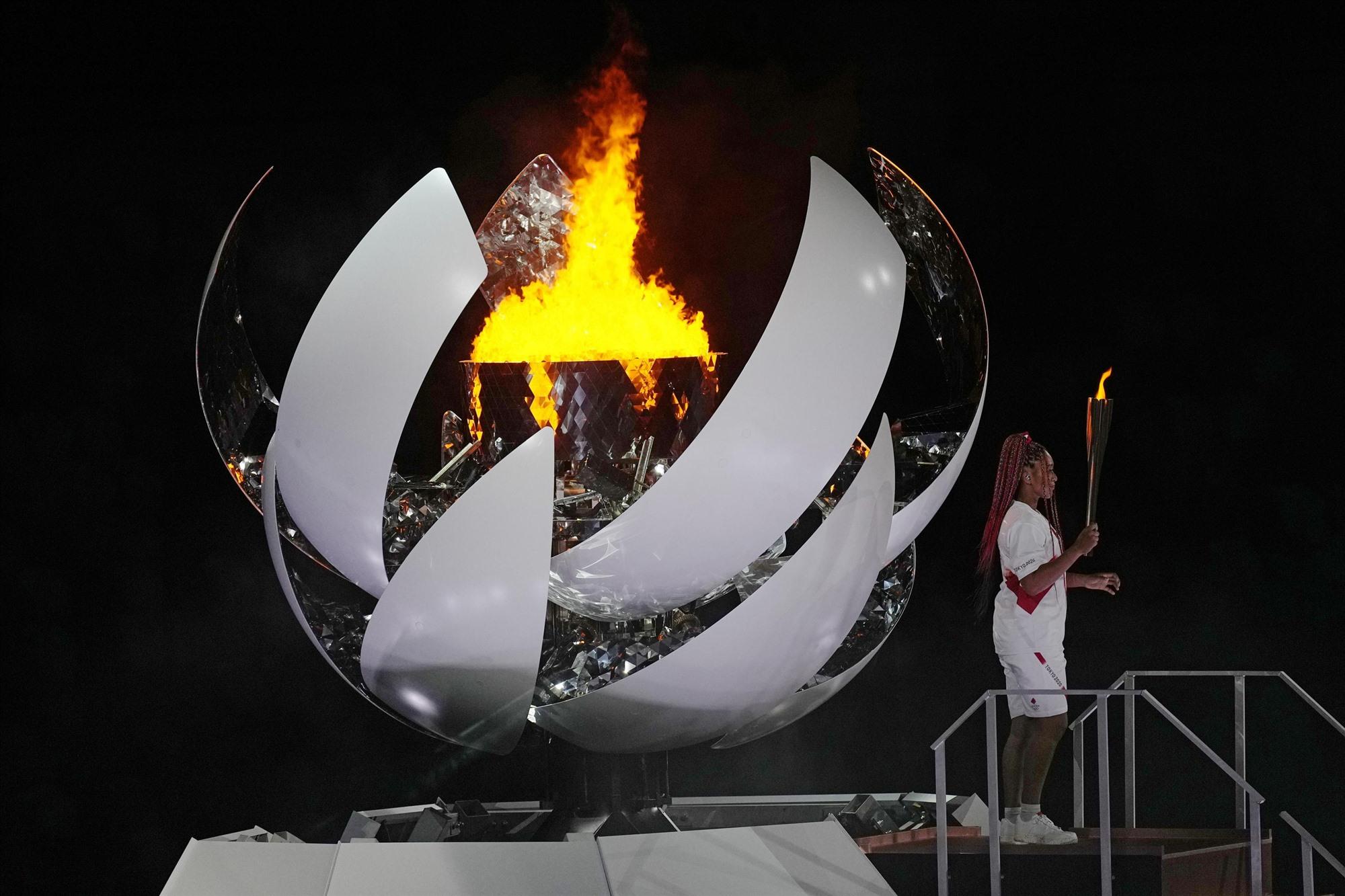 Vận động viên quần vợt Naomi Osaka thắp sáng ngọn lửa Olympic trong lễ khai mạc ngày 23.7. Ảnh: AP