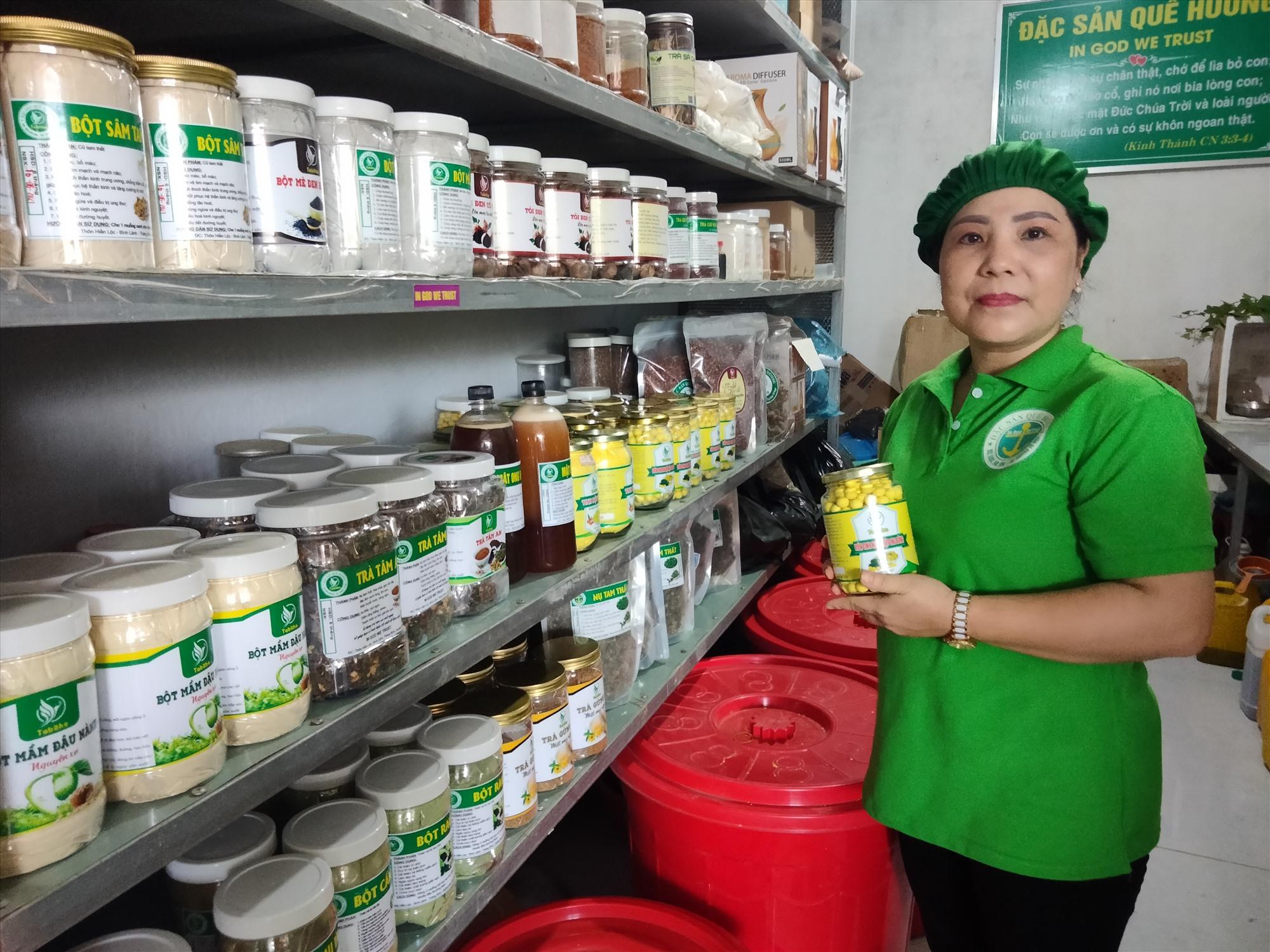Chị Đặng Thị Tố Nga bên sản phẩm viên tinh bột nghệ mật ong rừng. Ảnh: G.B