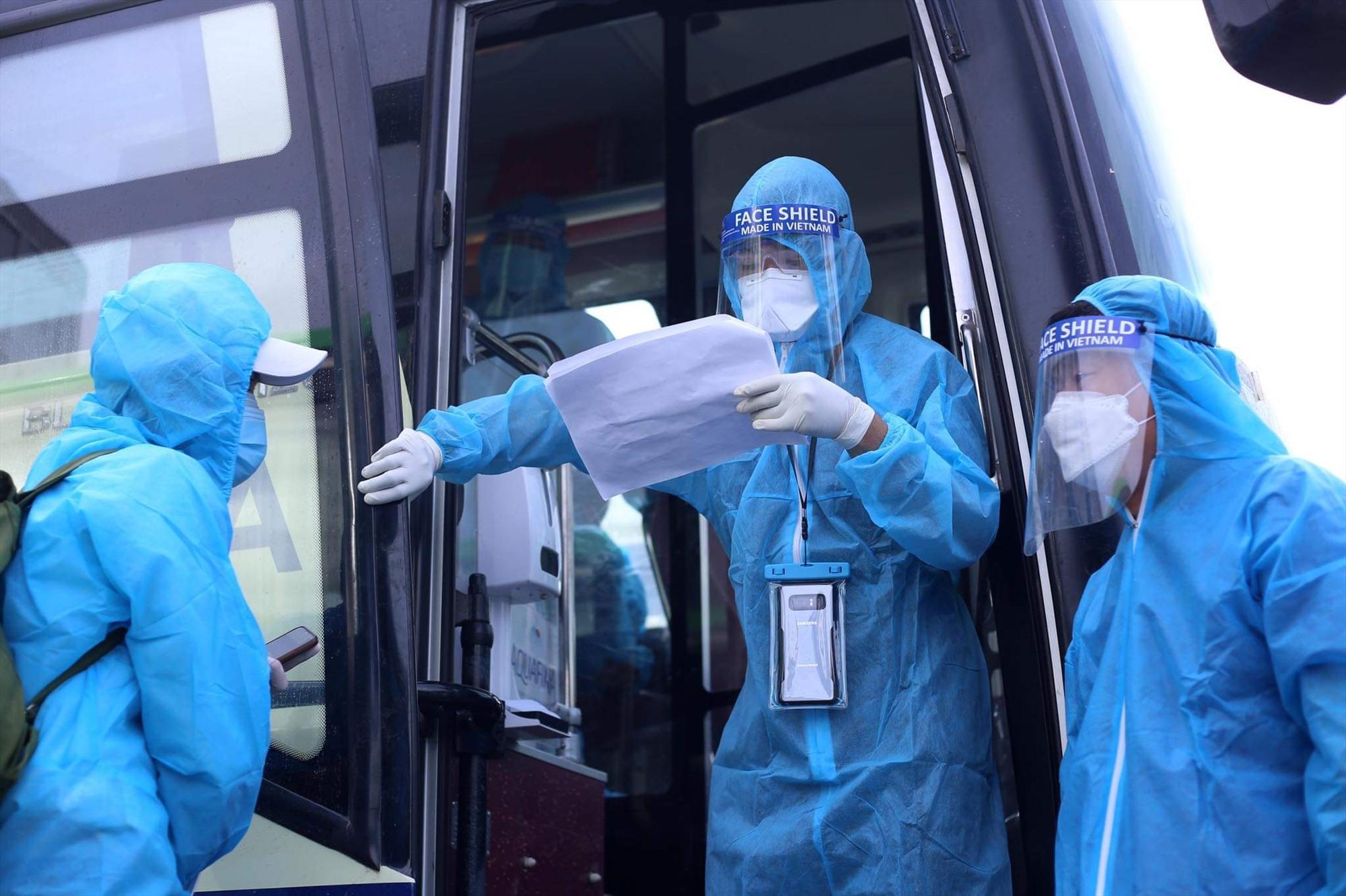 """Anh Dương Quang Dũng và cán bộ y tế kiểm tra thông tin """"hàng khách"""" trước khi lên xe."""