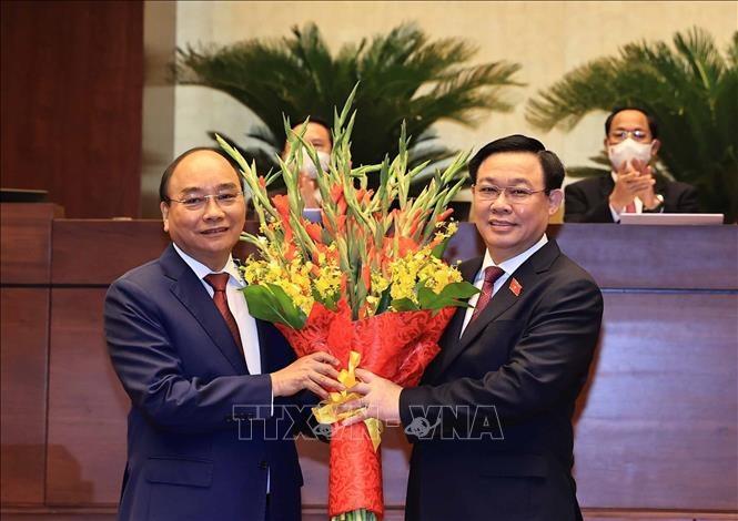Chủ tịch Quốc hội Vương Đình Huệ (phải) tặng hoa chúc mừng Chủ tịch nước Nguyễn Xuân Phúc. Ảnh: TTXVN