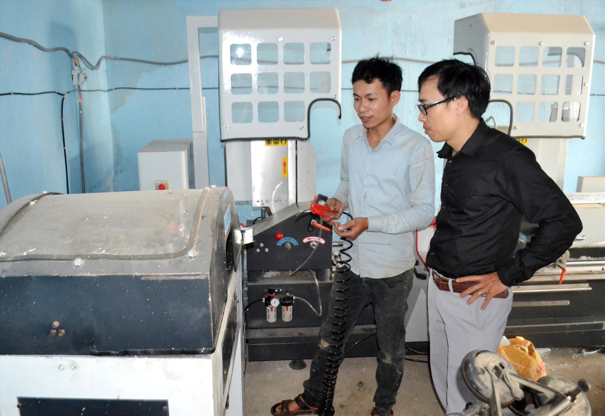 Anh Nguyễn Kim Đồng (áo sáng) ở thị trấn P'rao - điển hình lập nghiệp thành công - giới thiệu thiết bị ở cơ sở cửa nhôm của mình. Ảnh: KK