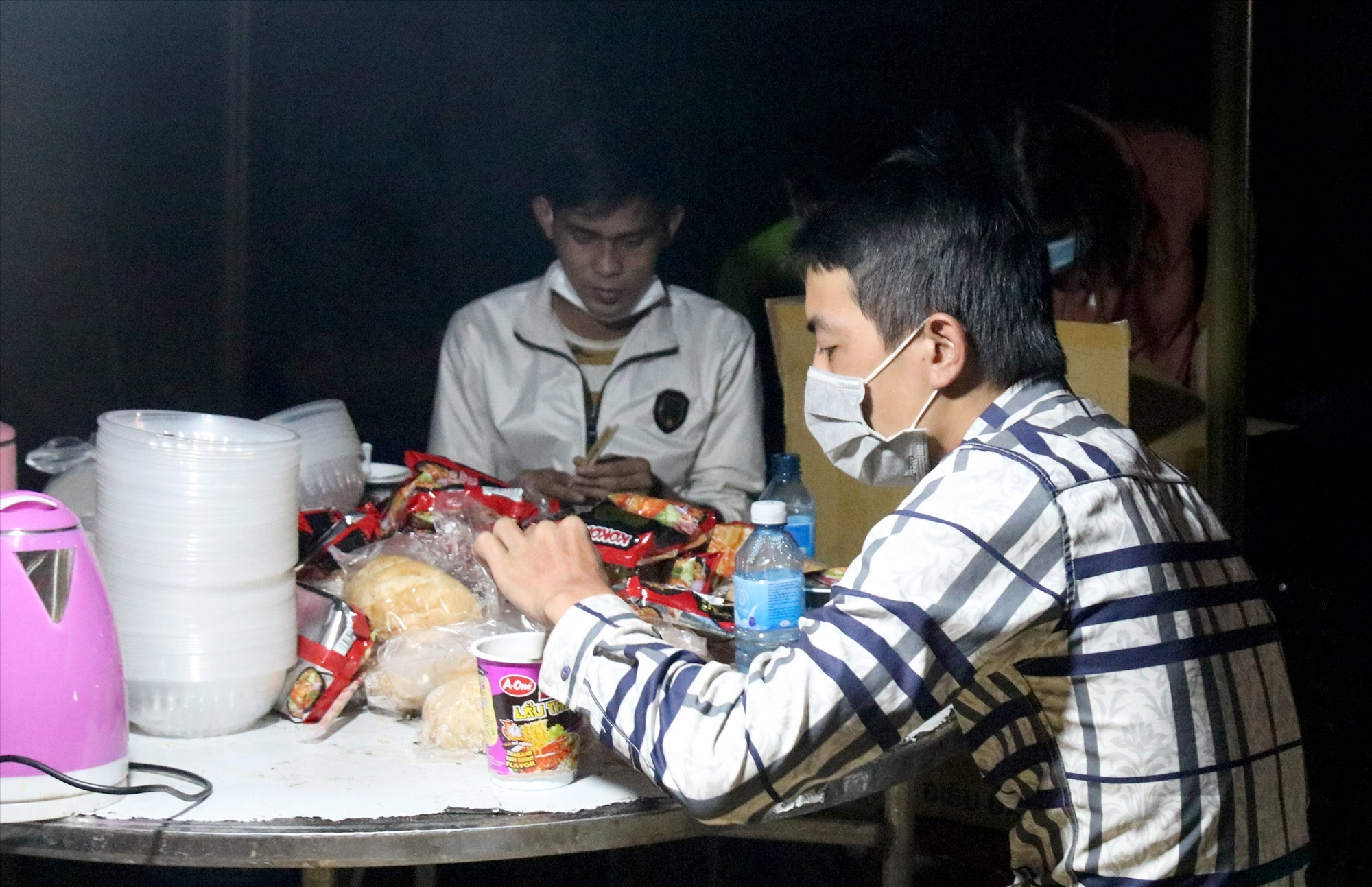 Người dân ăn vội mì gói, bánh mỳ để tiếp tục di chuyển qua địa bàn Quảng Nam trong đêm. Ảnh: H.Q