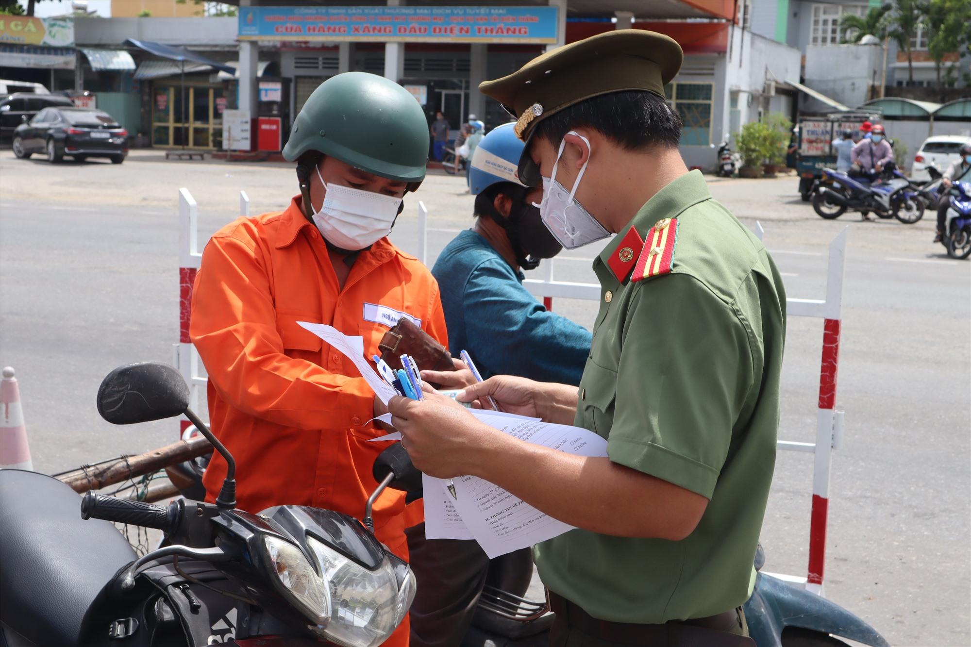Lực lượng chức năng kiểm tra giấy tờ tại một chốt kiểm soát cửa ngõ giữa Quảng Nam - Đà Nẵng. Ảnh: H.S