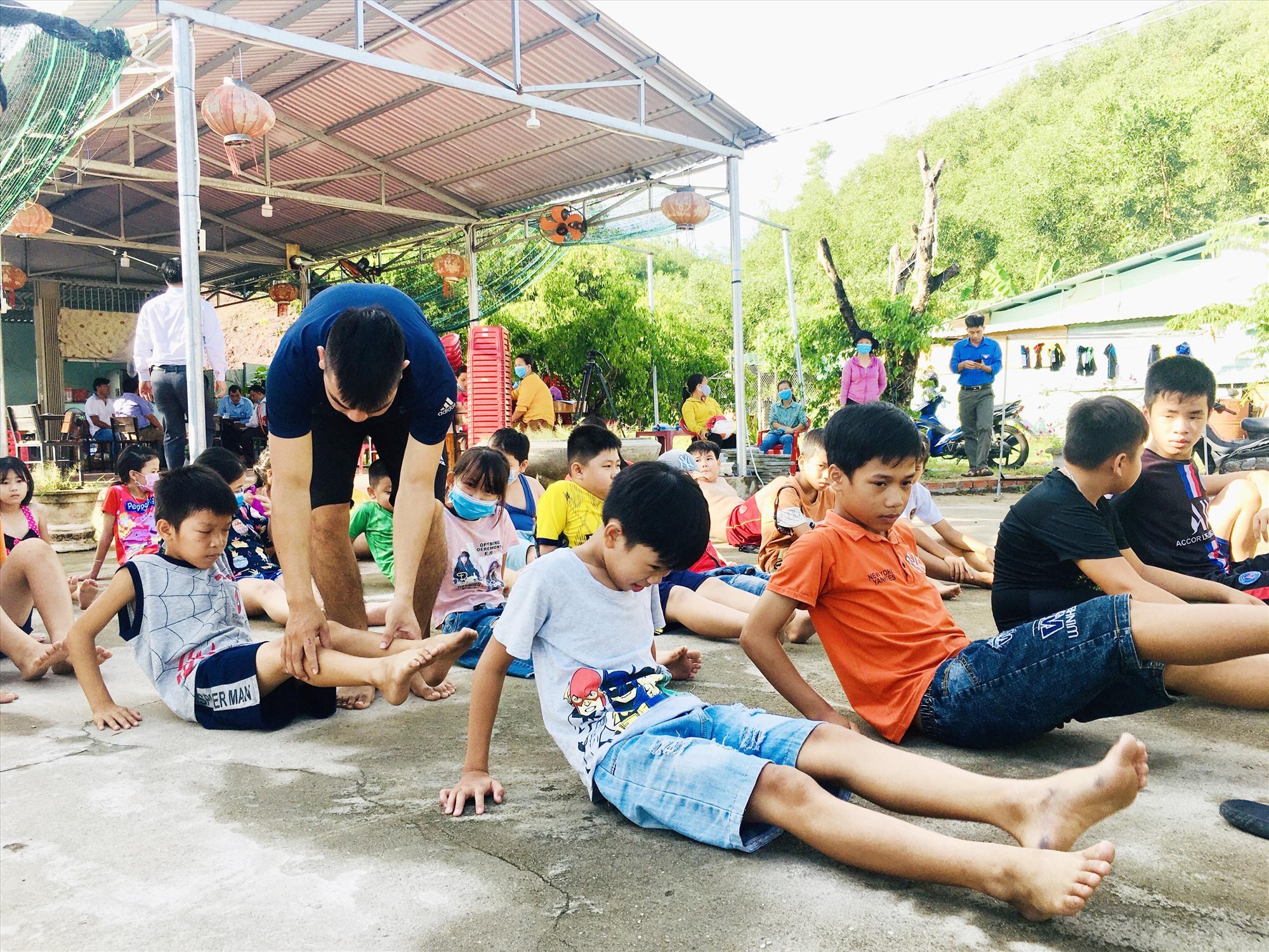 Trẻ em được trang bị những kỹ năng cần thiết, bổ ích thông qua các hoạt động hè. Trong ảnh: Trẻ em xã Quế Trung học các động tác khởi động trước khi bơi. Ảnh: TÂM LÊ