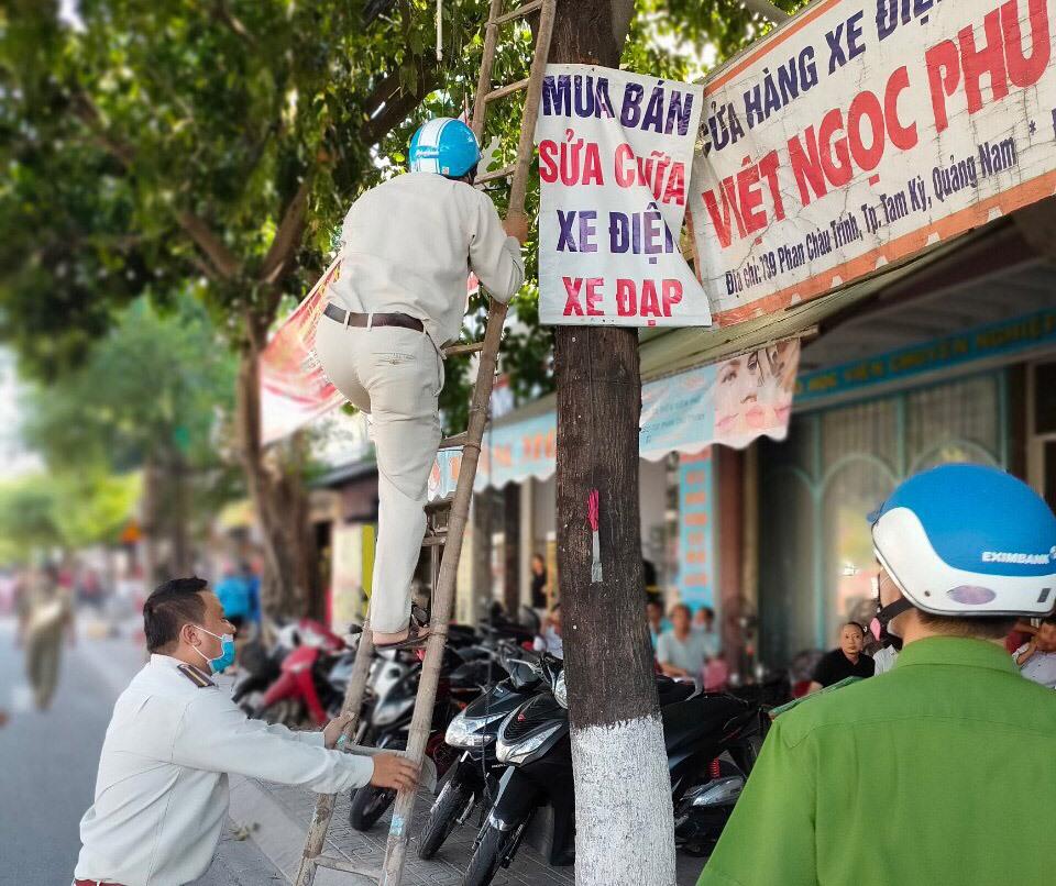 Tổ trật tự đô thị phường Hòa Hương (TP.Tam Kỳ) tháo dỡ biển quảng cáo treo trên cây xanh đô thị. Ảnh: T.T