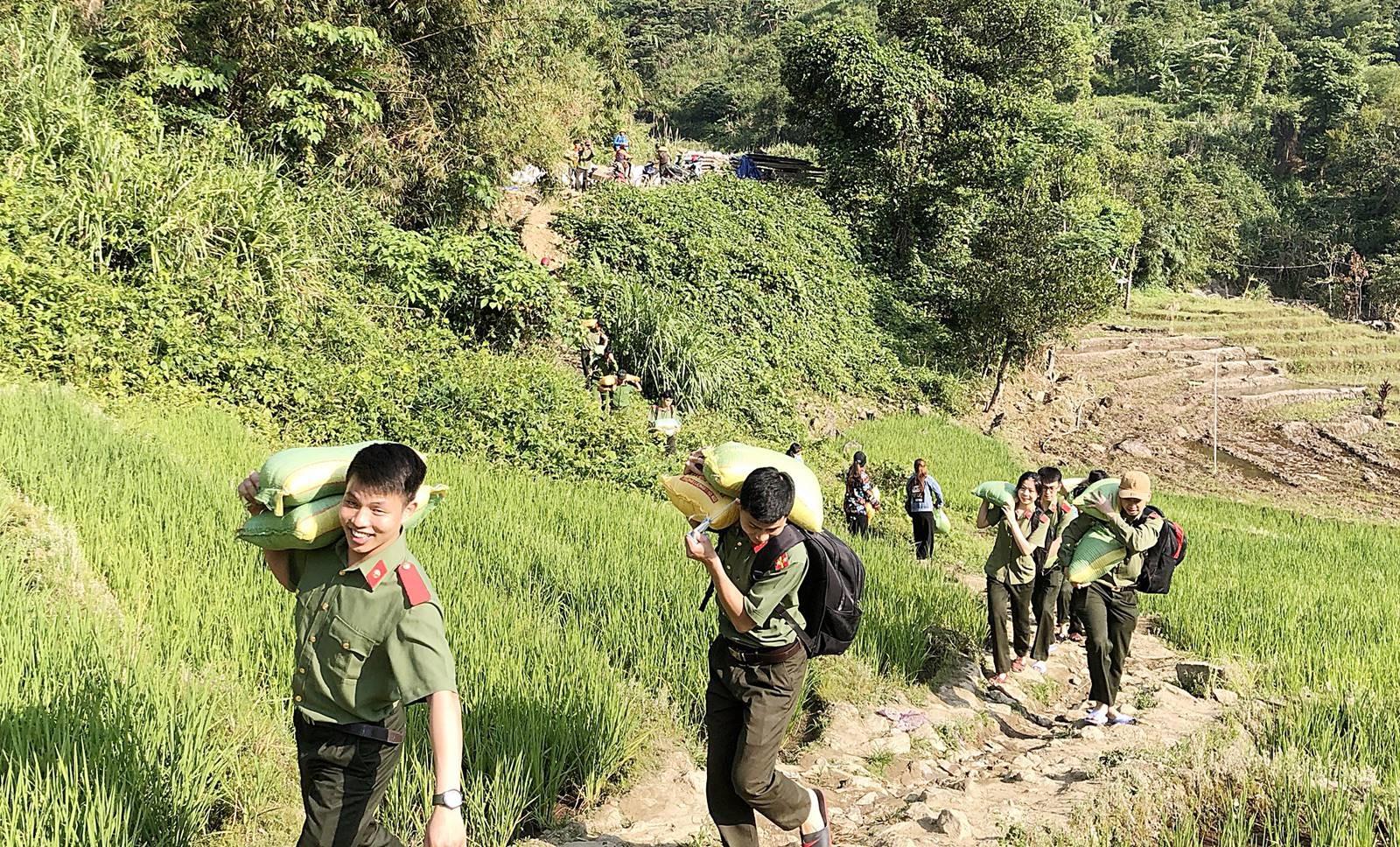 Tuổi trẻ lực lượng An ninh cõng gạo hỗ trợ đồng bào xã Trà Nam, huyện Nam Trà My. Ảnh: Công an Nam Trà My.