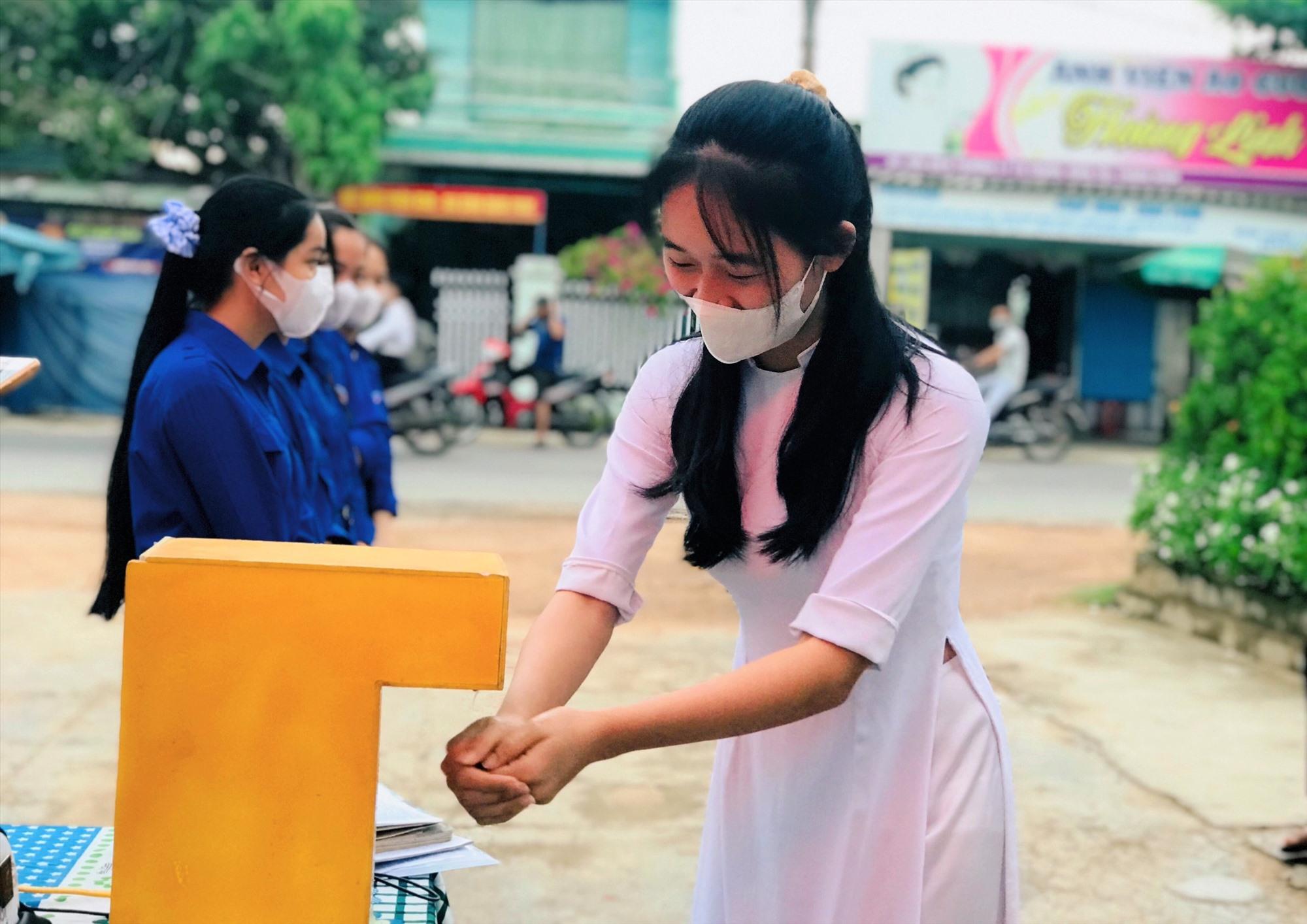 Thí sinh rửa tay sát khuẩn bằng máy sát khuẩn tự động tại điểm thi Trường THPT Lý Tự Trọng (xã Bình Trị, huyện Thăng Bình). Ảnh: VĂN ĐỨC