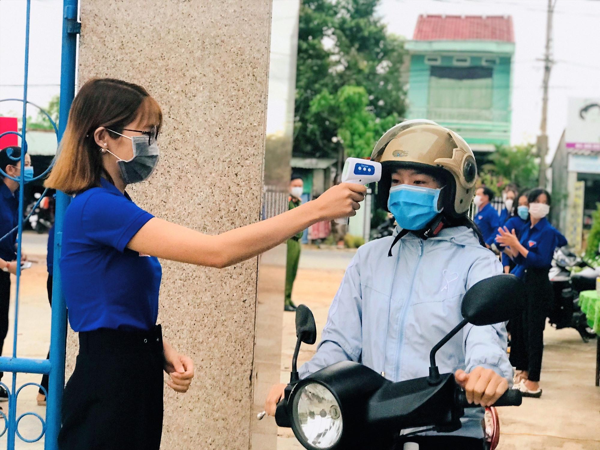 Thanh niên tình nguyện huyện Thăng Bình hỗ trợ đo thân nhiệt tại khu vực thi tốt nghiệp THPT. Ảnh: CTV
