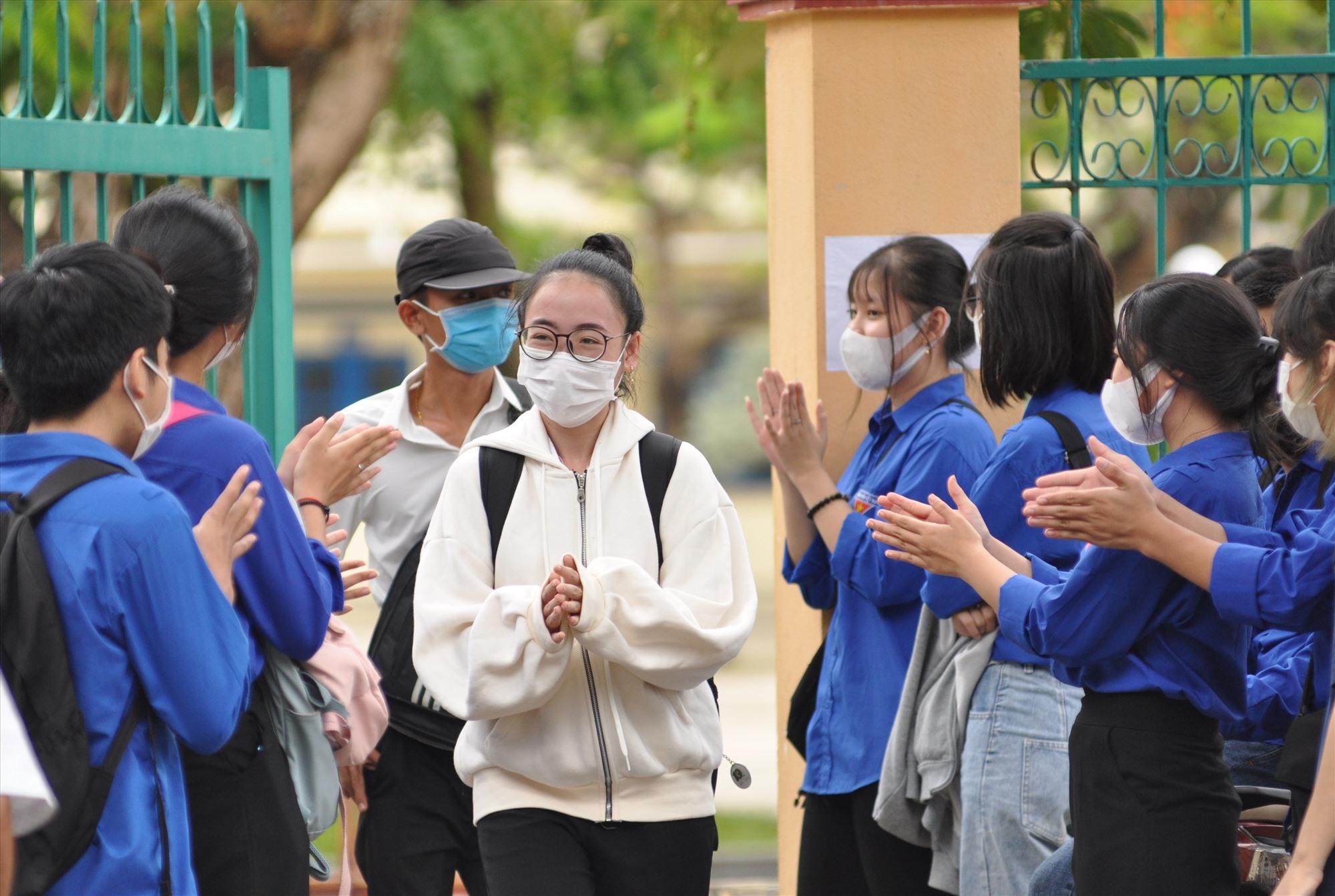 Học sinh tình nguyện chúc mừng thí sinh đầu tiên hoàn thành bài thi. Ảnh: X.P