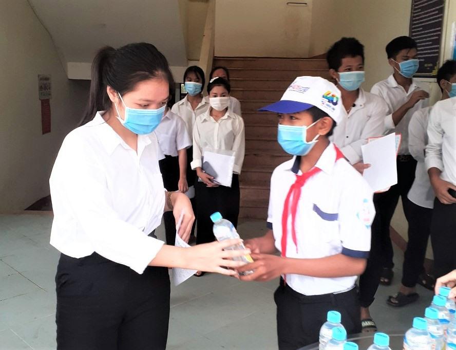 Em Pơloong Phan Hiếc đeo khăn quàng, cùng tham gia tiếp sức các anh chị thí sinh. Ảnh: Đ.N