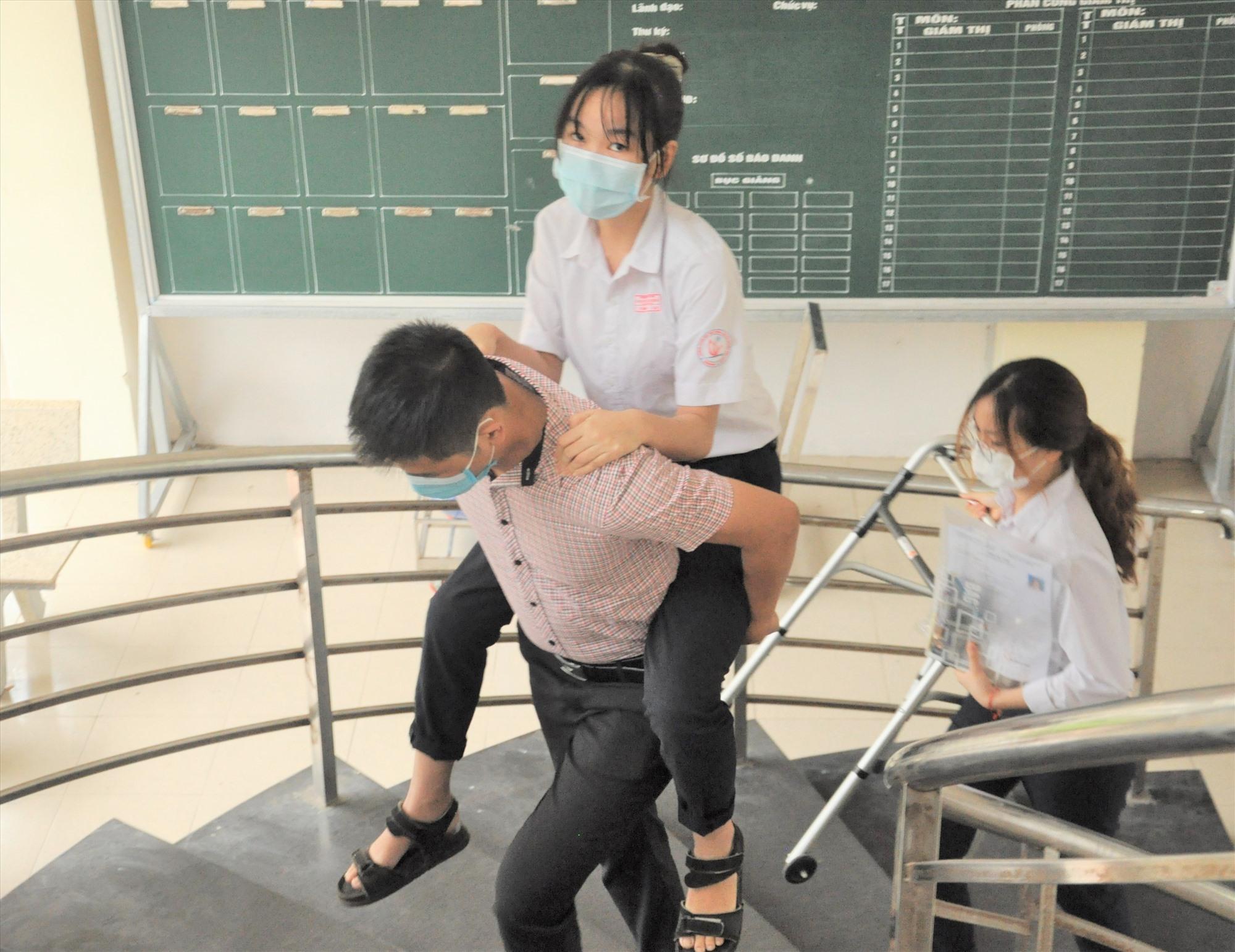 Thí sinh Lê Thị Bình Thạnh, học sinh lớp chuyên Văn Trường THPT chuyên Nguyễn Bỉnh Khiêm bị tai nạn giao thông gãy chân được một cán bộ làm công tác thi cõng lên phòng thi nơi tầng 2. Ảnh: X.P