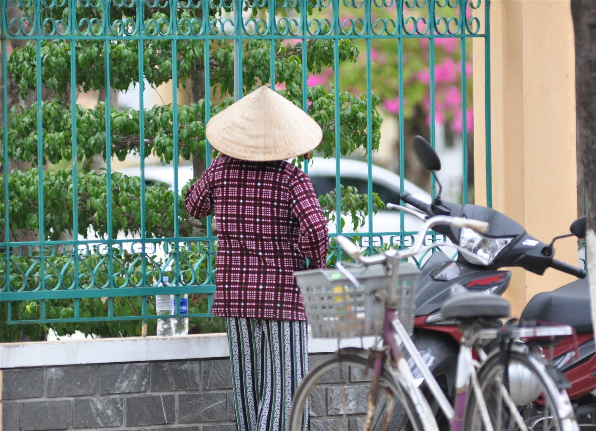 Con thi âu lo một, mẹ âu lo mười. Mẹ đi xe đạp đến đứng ngoài hàng rào ngóng con đang thi tại điểm thi Trường THPT Phan Bội Châu (Tam Kỳ). Ảnh: X.P