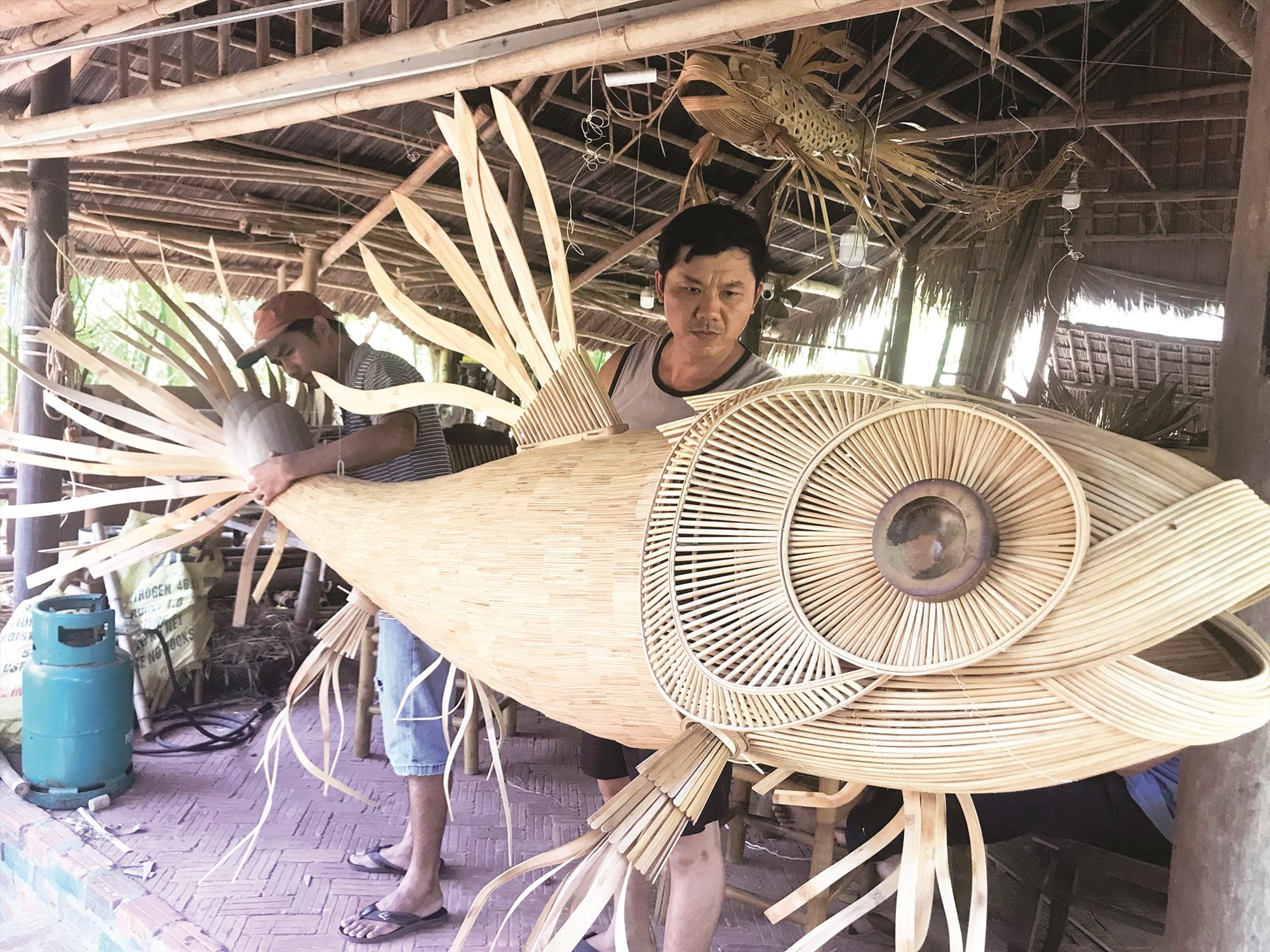 Anh Tân cùng thợ đang gấp rút hoàn thành chiếc đèn lồng hình cá Koi để giao cho khách.