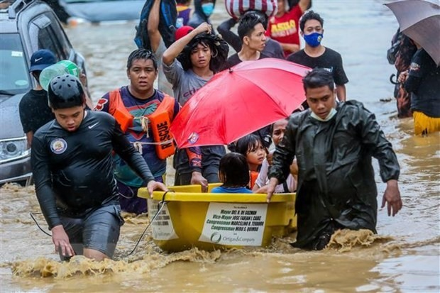 Rescuers help people in Manila, Philippines evacuate due to Storm Vamco (File photo: Xinhua/VNA)