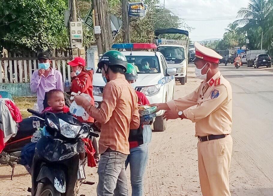 Lực lượng chức năng tỉnh hướng dẫn, hỗ trợ người dân về từ vùng dịch bằng xe máy đoạn qua địa bàn huyện Phước Sơn. Ảnh: CTV