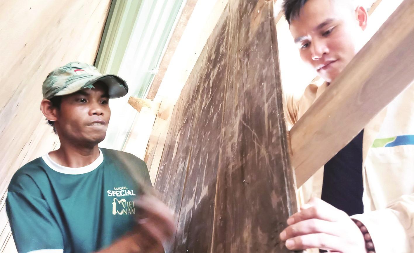 Anh Hồ Văn Hóa (bên trái) cùng em trai đóng những tấm phên - nguyên liệu được tận dụng từ ngôi nhà ở làng cũ.