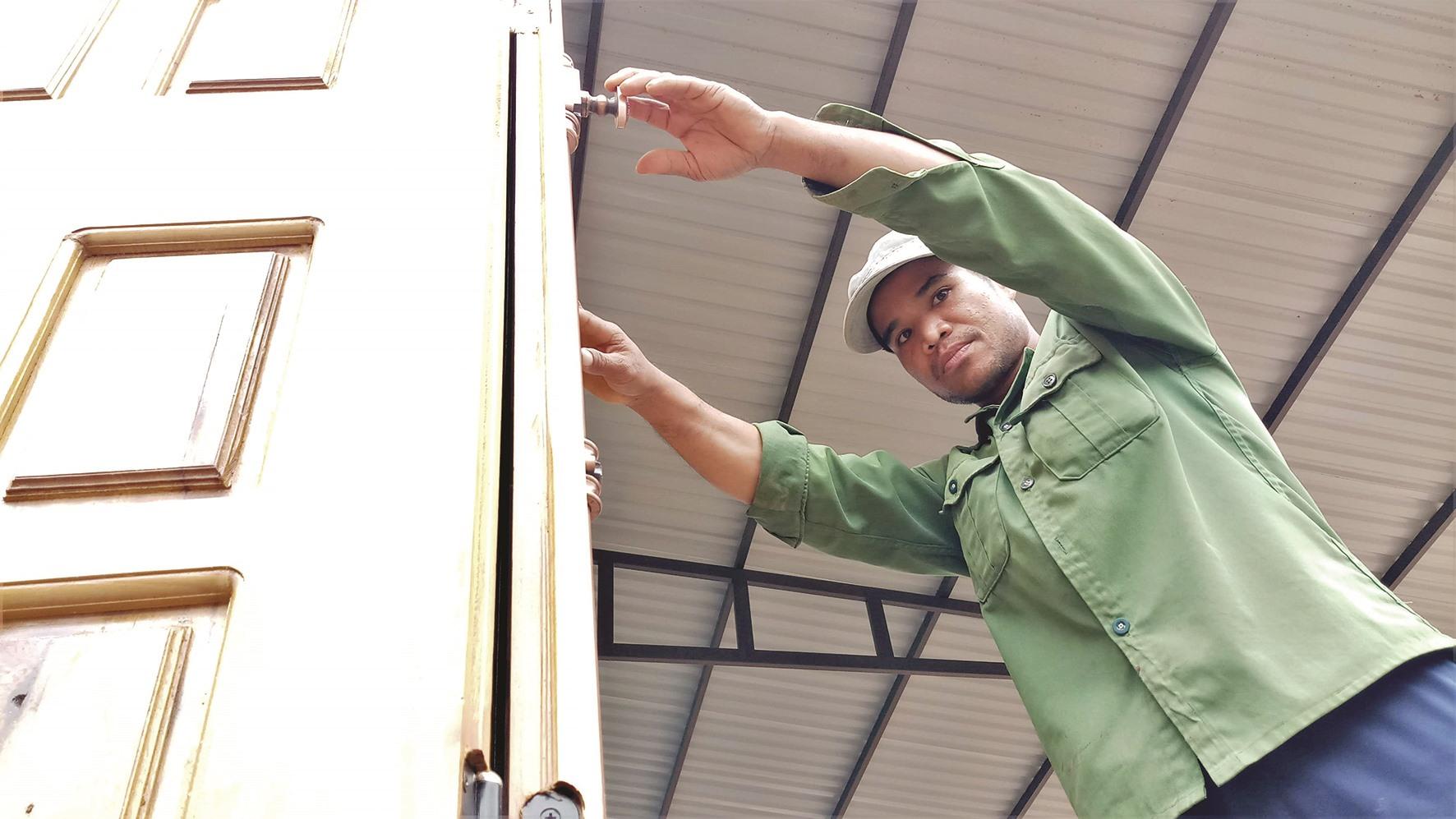 Ông Hồ Văn Minh kiểm tra cửa nhà trong buổi chính quyền địa phương đến nghiệm thu. Ông Minh nói, hiện khu tái định cư vẫn còn thiếu điện và nước sinh hoạt.
