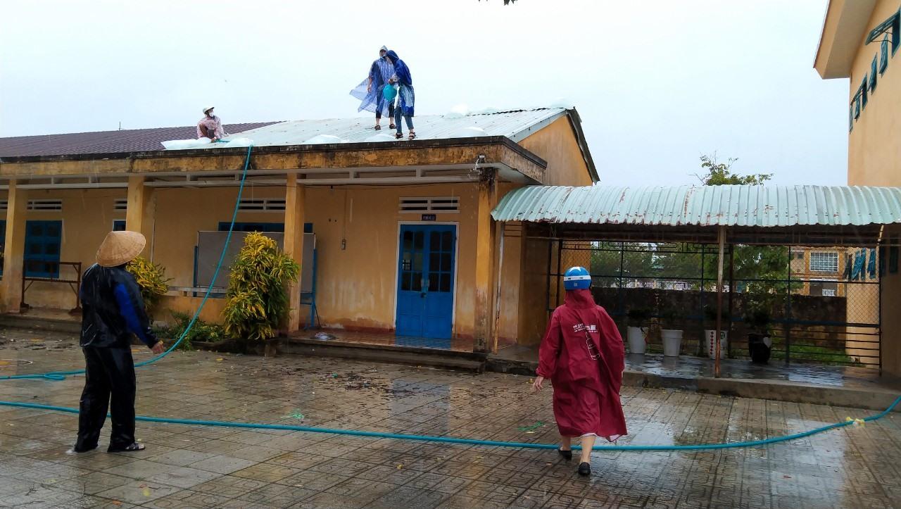Người dân thực hiện gia cố mái nhà để hạn chế thiệt hại do bão số 5 gây ra. Ảnh: N.H.LAI