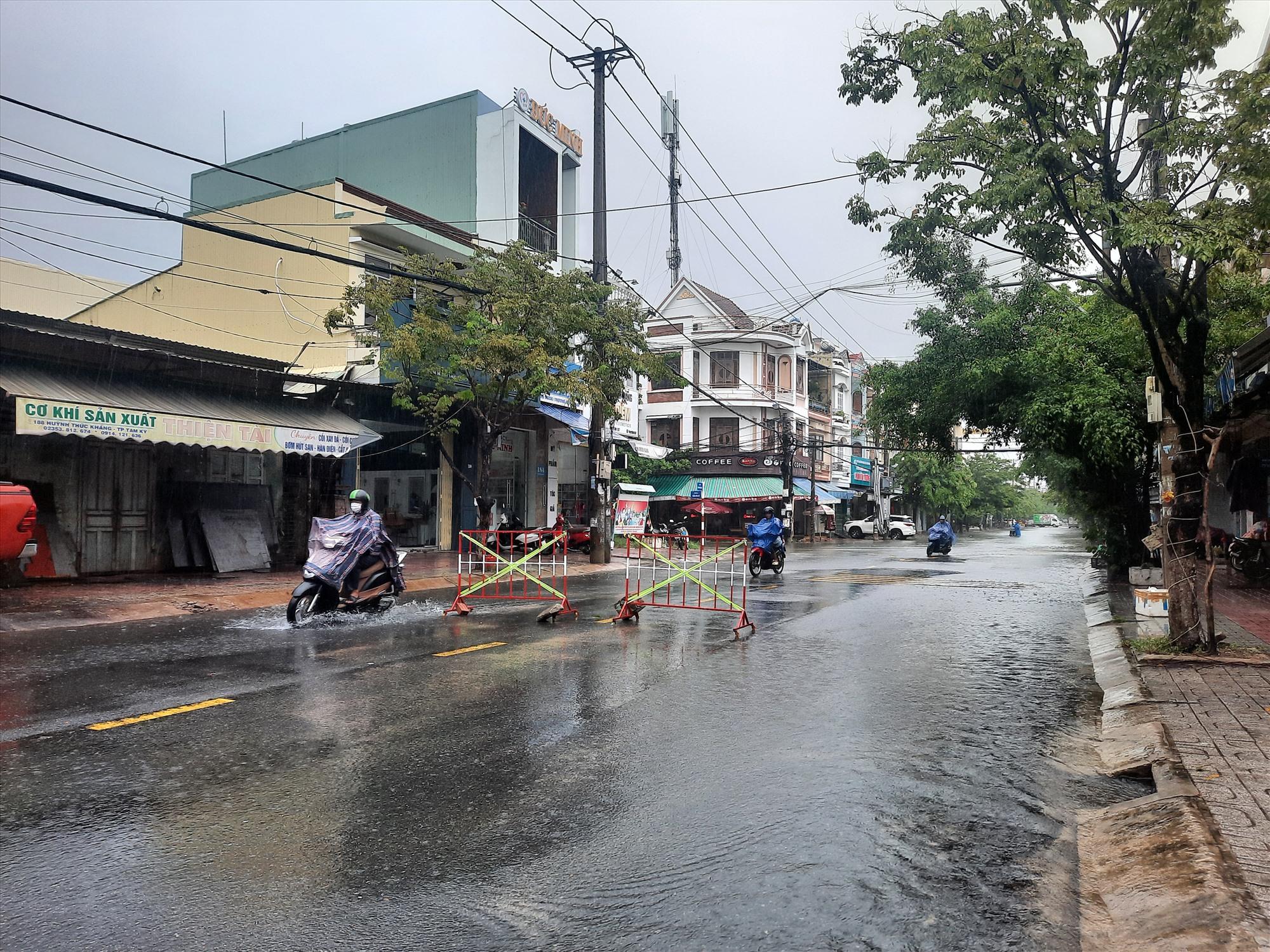 Lực lượng chức năng TP.Tam Kỳ đặt biển cảnh báo trên tuyến đường Huỳnh Thúc Kháng đang ngập sâu. Ảnh: H.Q