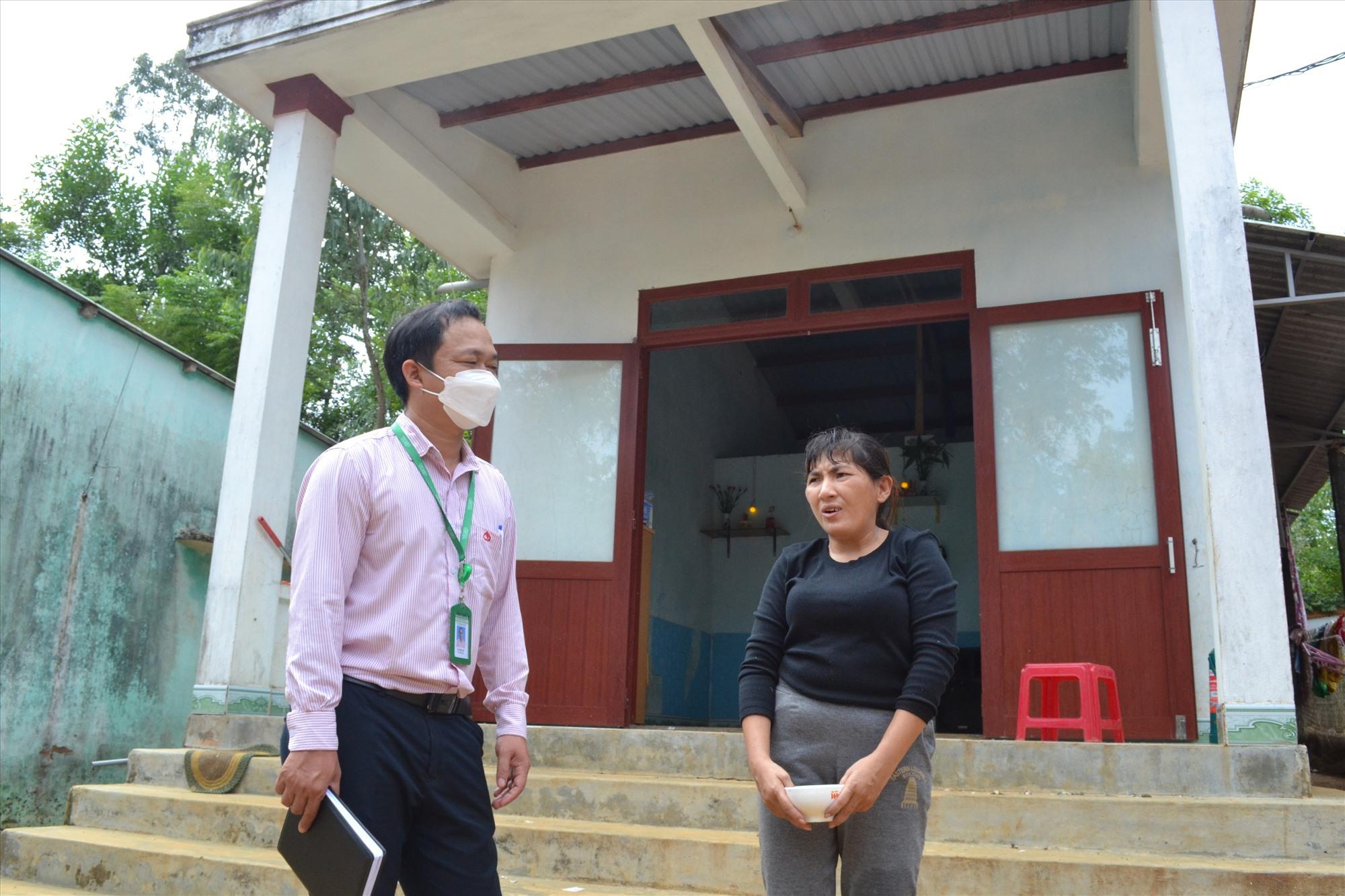Cán bộ Phòng giao dịch Ngân hàng CSXH huyện Núi Thành trao đổi với bà Trần Nguyên Trinh về xây dựng mô hình kinh tế hiệu quả để thoát nghèo. Ảnh: VIỆT NGUYỄN